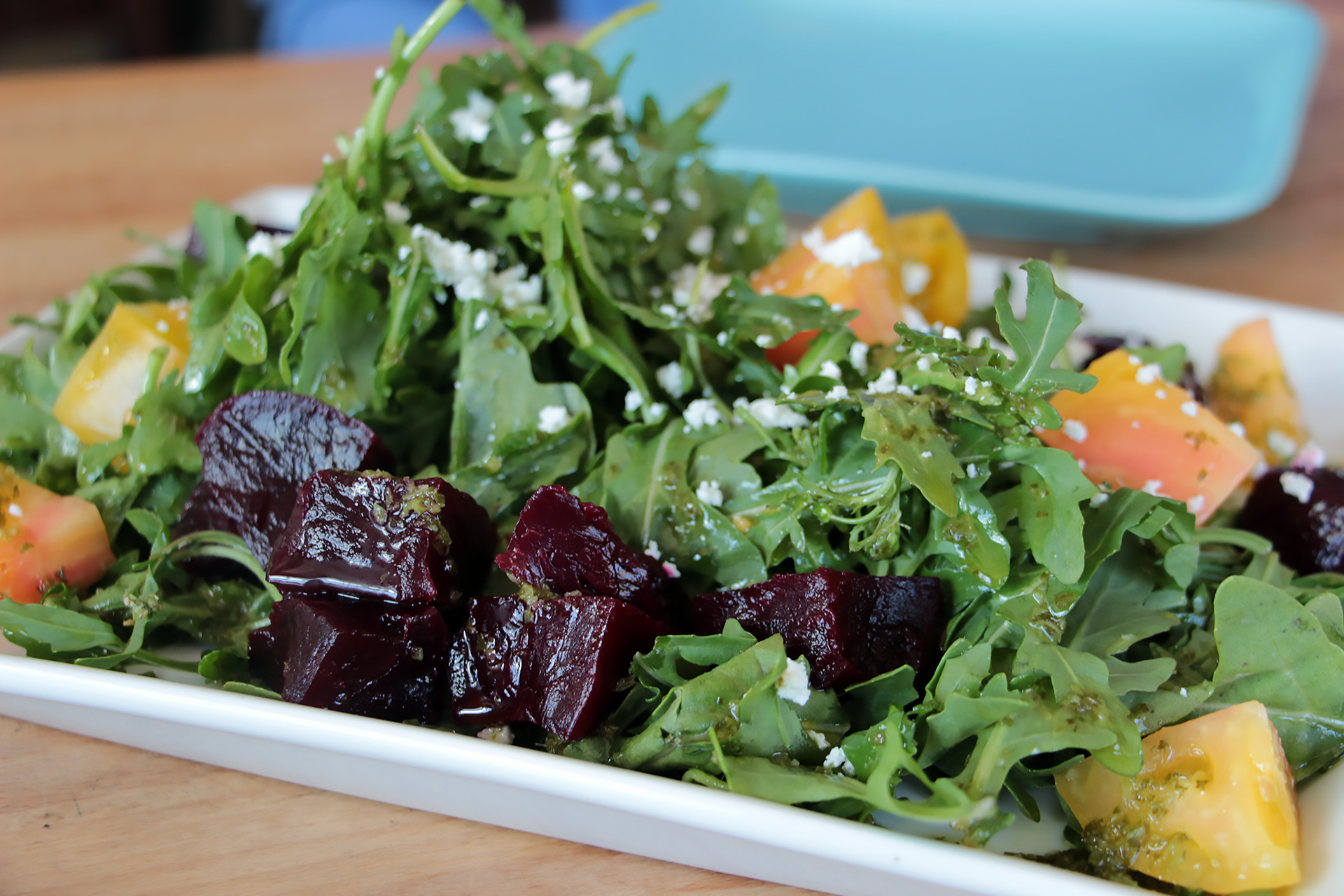 Arugula salad with roasted beets, early summer tomatoes, scattered goat cheese and a pesto sauce.
