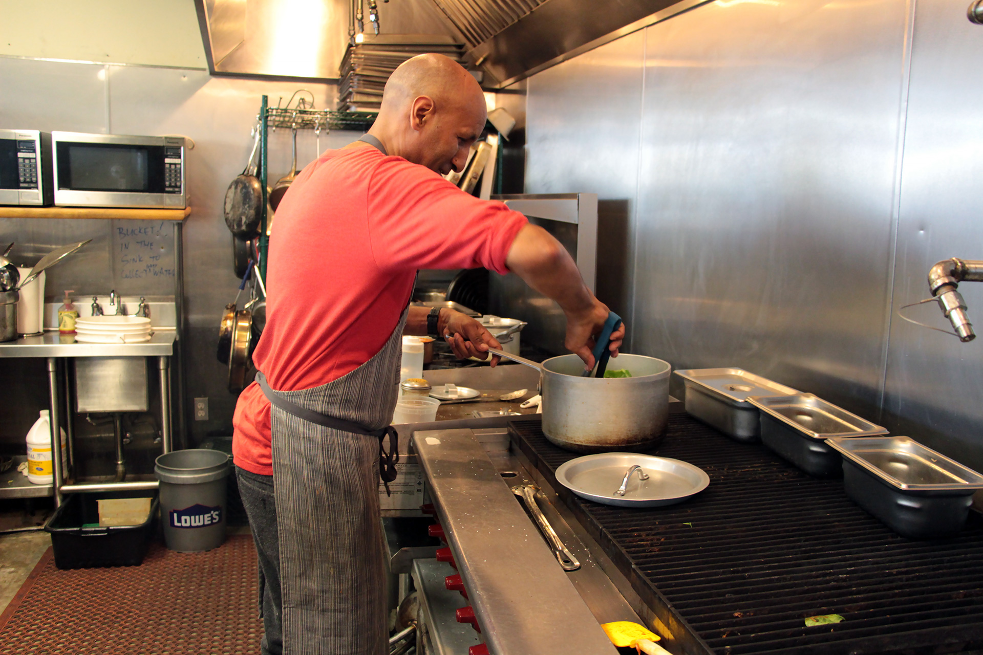Eskender Aseged, owner/chef at Radio Africa, cooking in the kitchen.
