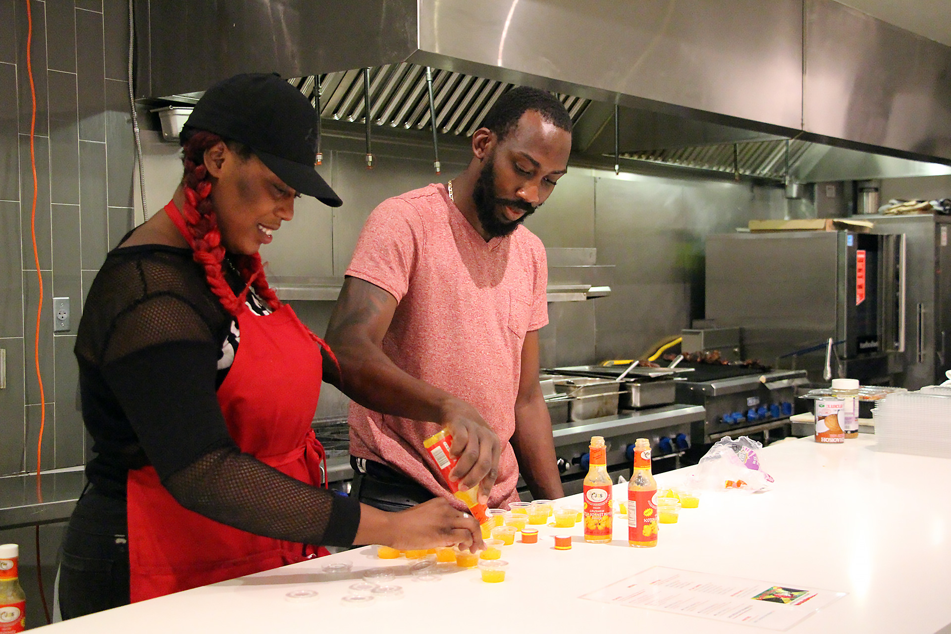Co-owner and Chef OB Matterson (R) and staff filling containers with Scotch Bonnet Pepper Sauce.