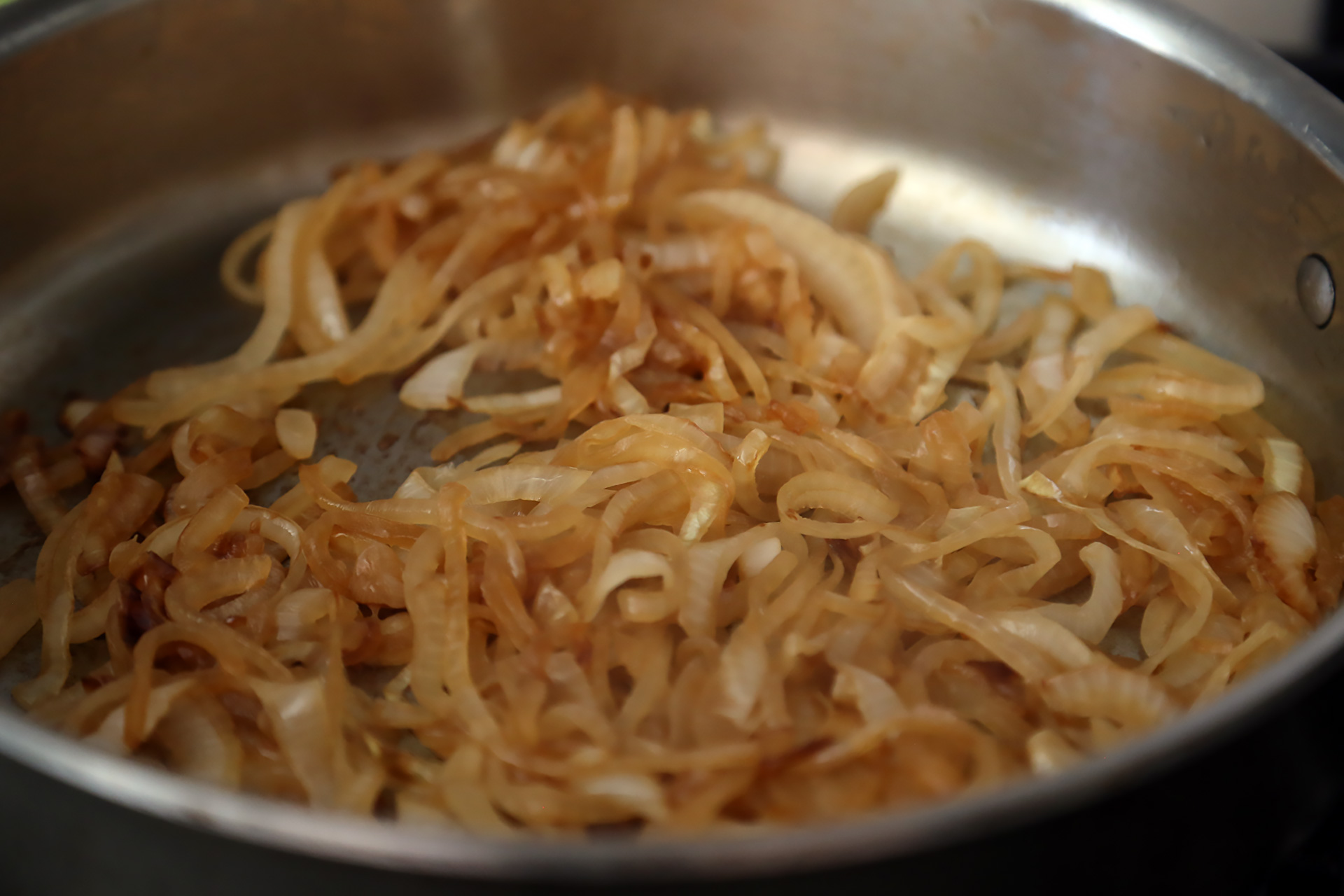 In a large saute pan over medium heat, warm the oil. Add the onions and a pinch of salt and cook, stirring, until they start to caramelize, about 15 minutes. Transfer to a bowl.