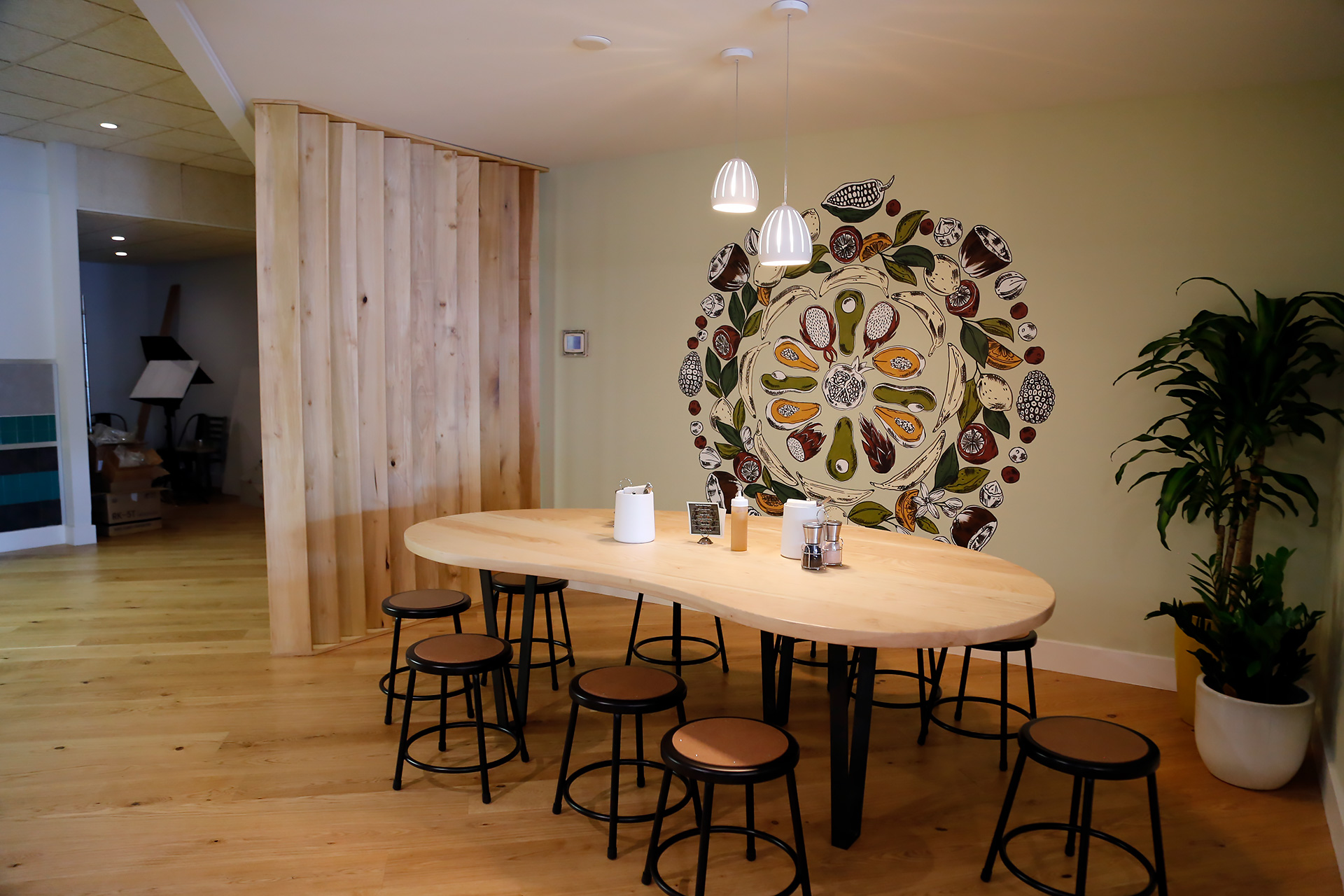 Large dining table with mural painted by local artist Megan Stevens from What Meg Creates.