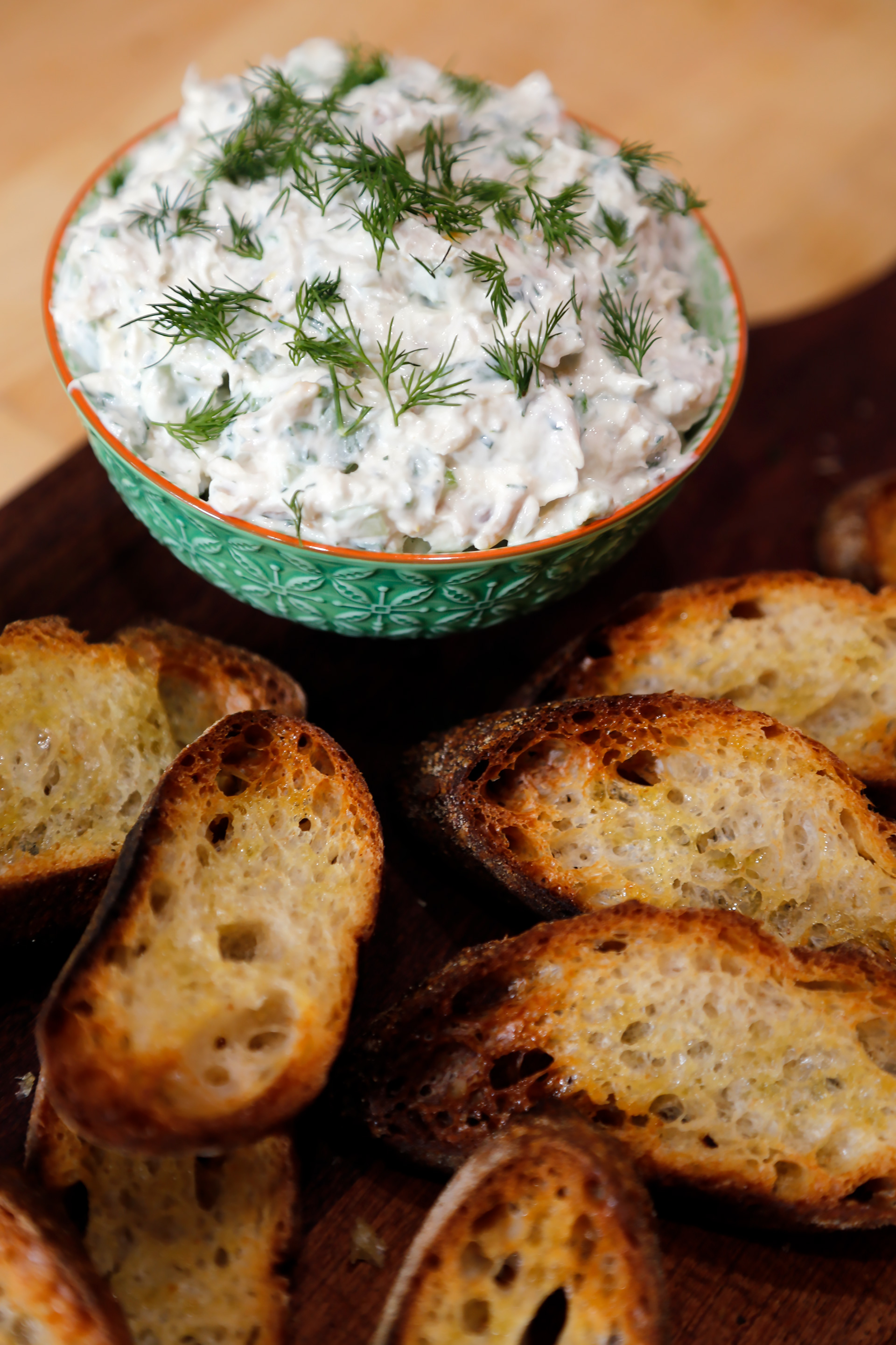 Garnish with dill and serve the Smoked Trout-Herb Dip with Crostini.