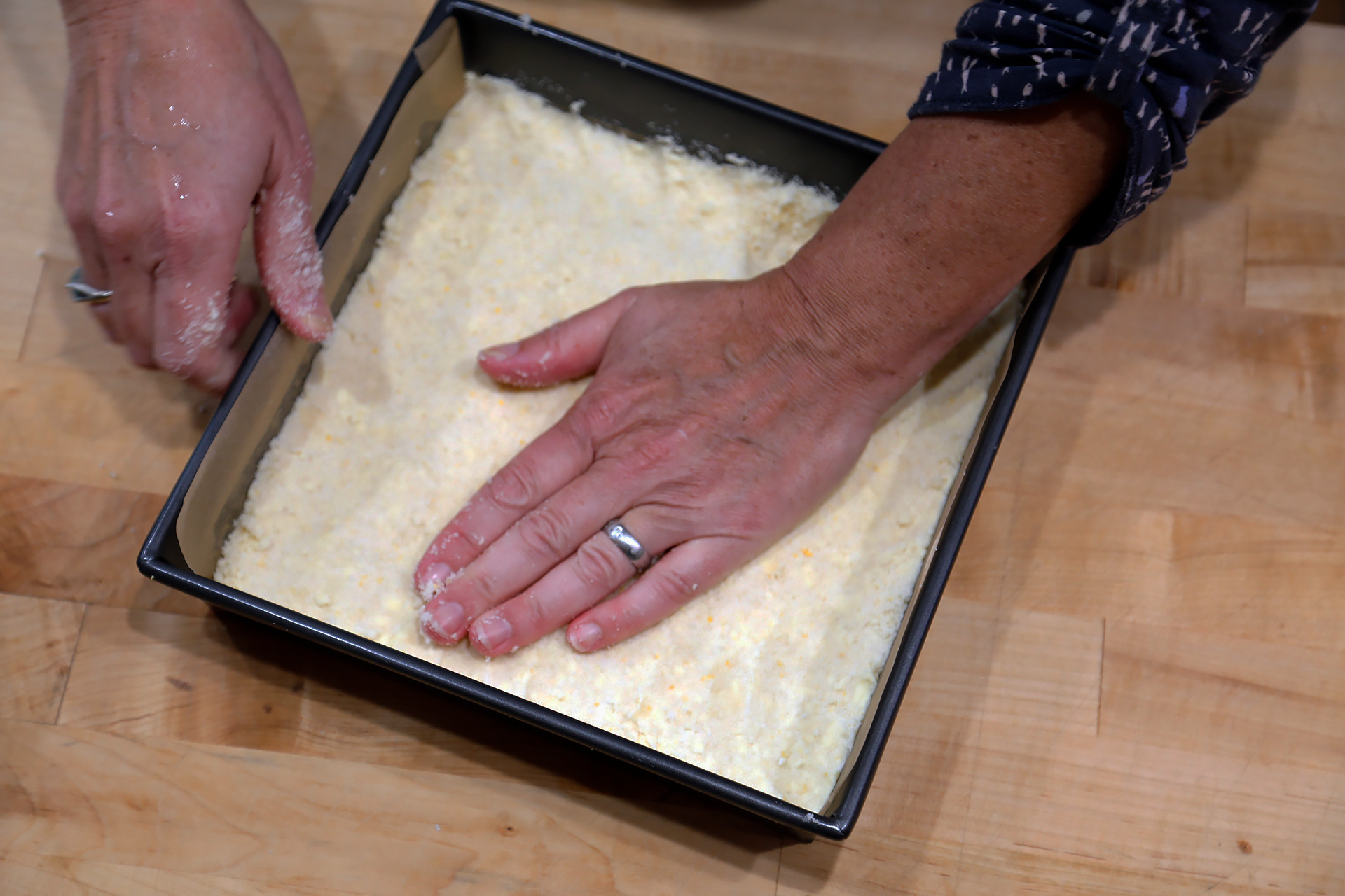 Press the dough into the prepared cake pan. Then sprinkle with 1 tbsp sugar.