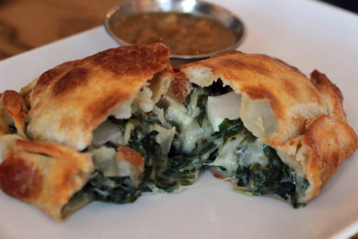 El Sur's vegetarian verde empanada with Swiss chard, spinach, onion, cheese sauce, olive and egg