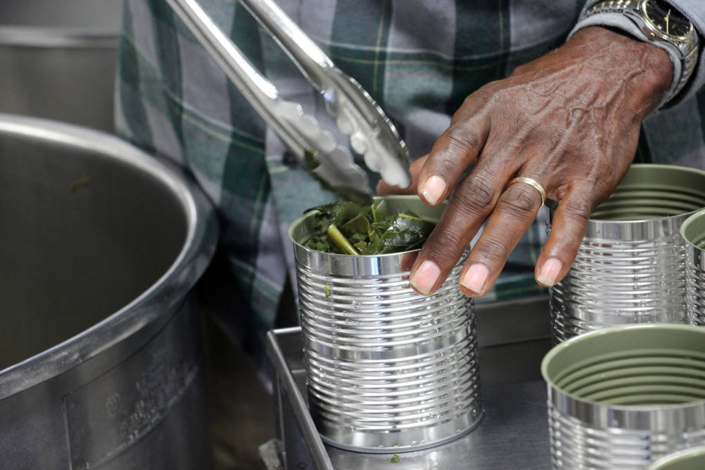 Roy Miller fills cans with cooked collard greens.