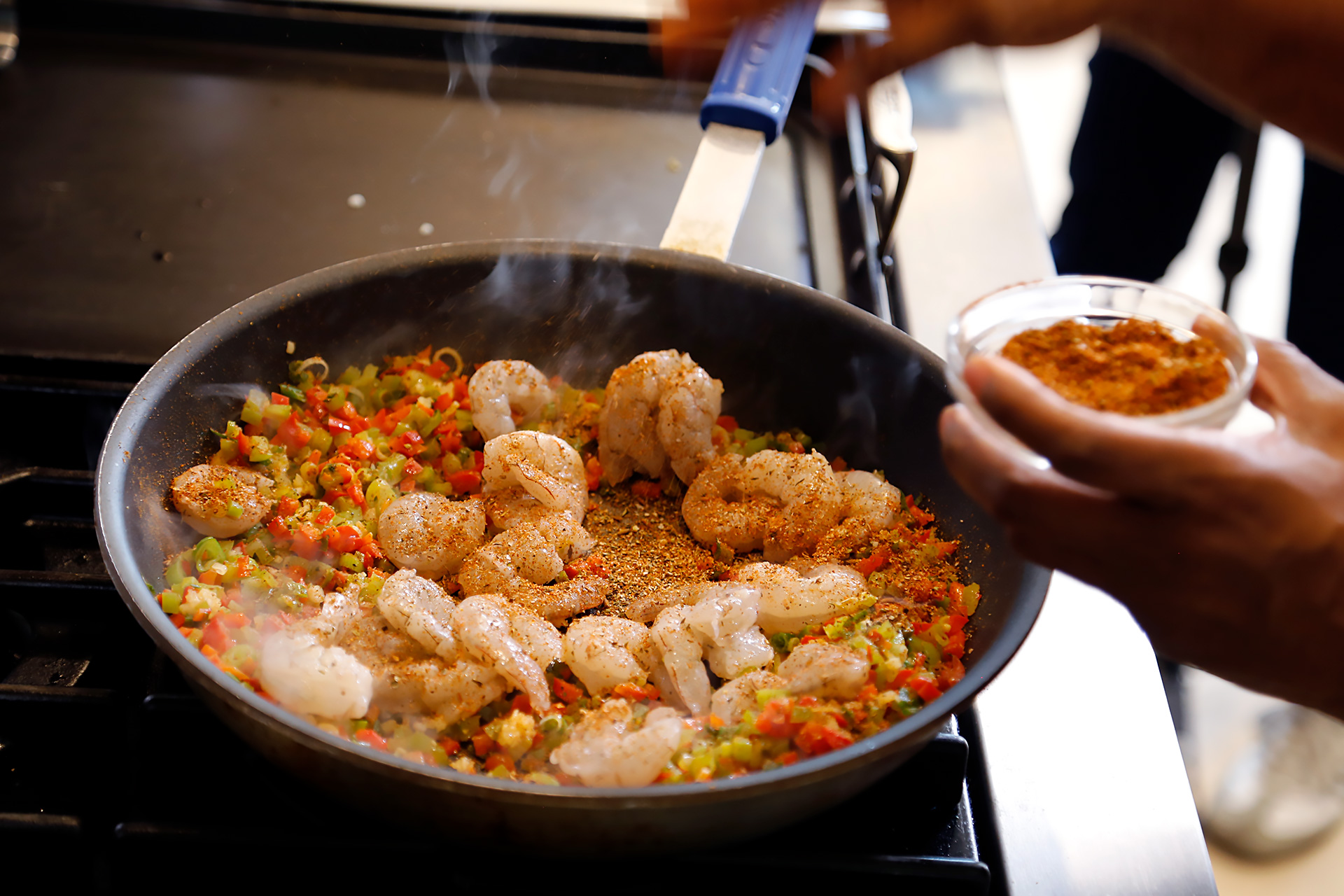 Turn shrimp and sprinkle with Creole spice then sauté until vegetables are softened, about five minutes.