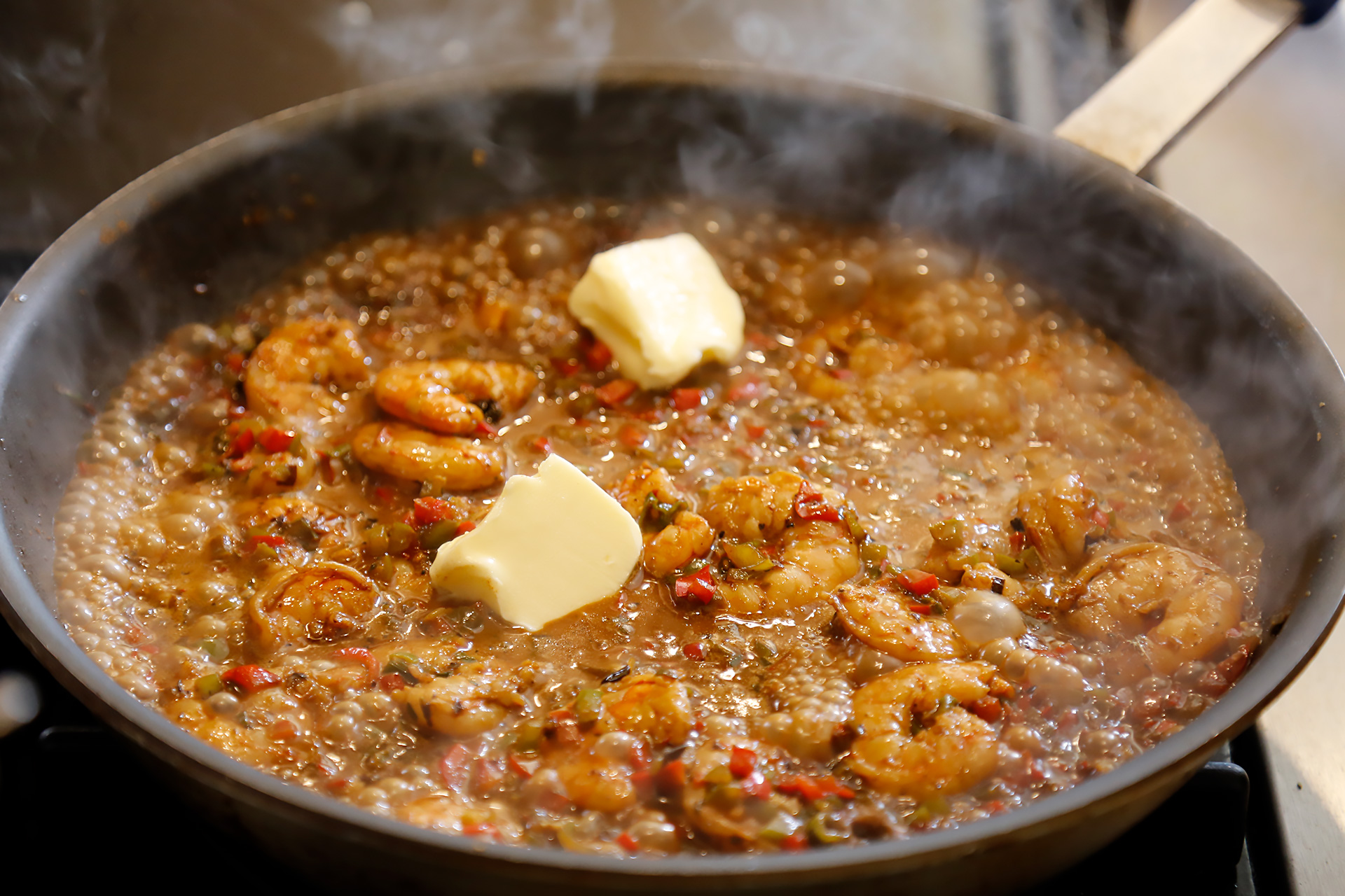 Add Creole sauce and cream, and bring to a simmer. When shrimp are cooked through, add butter and lemon juice.