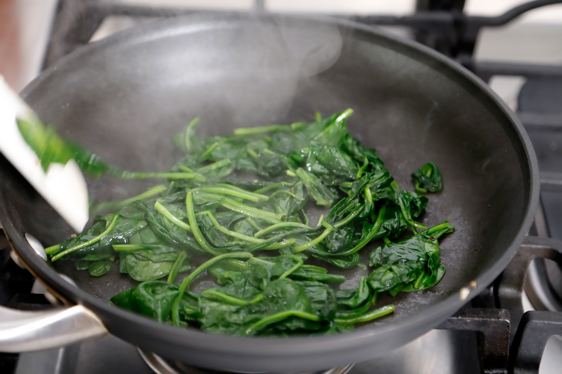 Add the spinach. Cook just until wilted, then transfer to a colander.