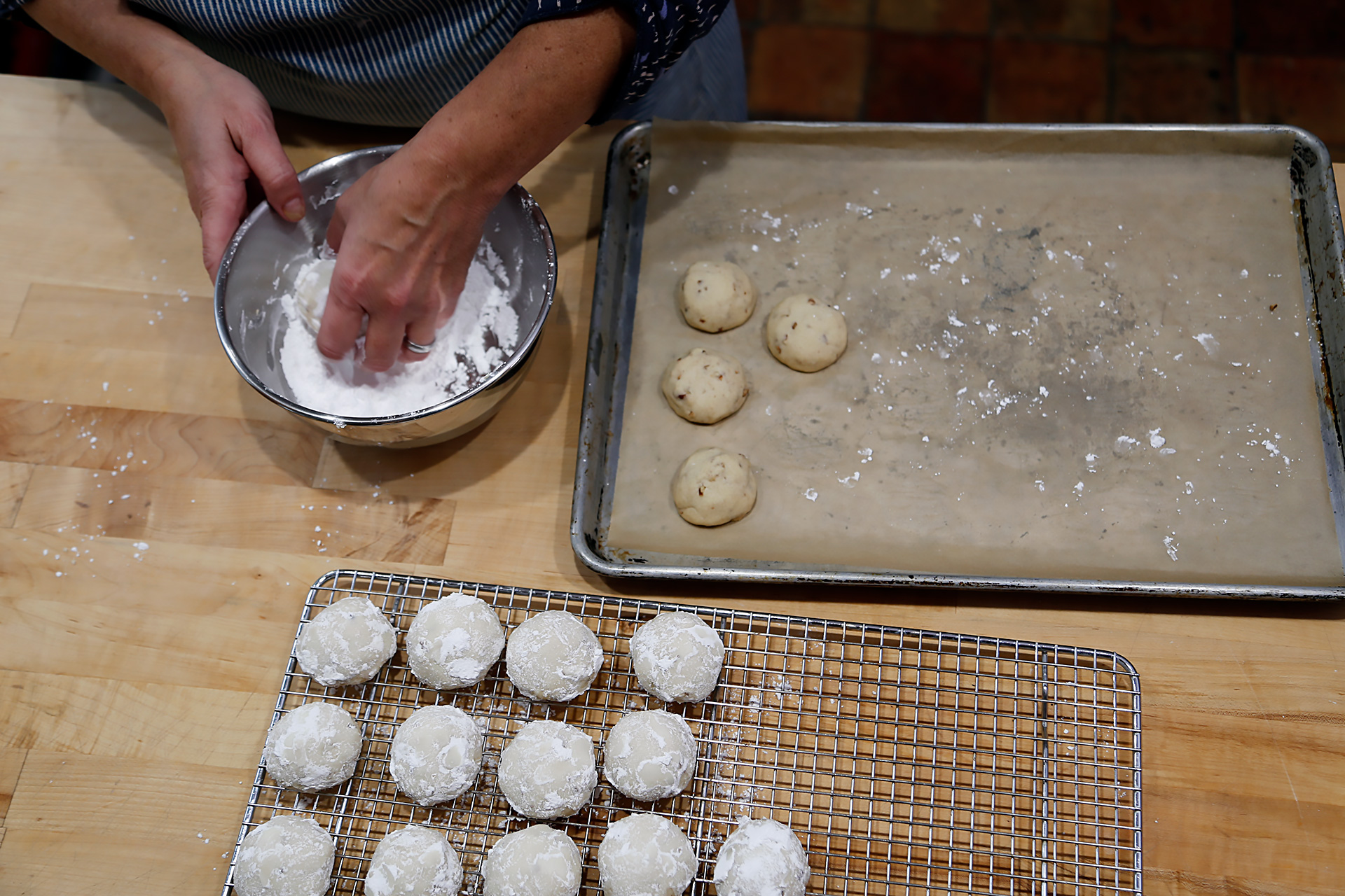 When cool enough to handle, roll the cookies in the reserved powdered sugar.