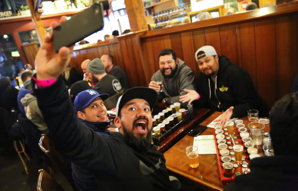 Victor Arrazabal, foreground, shoots a selfie with Sergio Guadron, left, Hernan Tobar, and Victor Arana, at the Russian River Brewing Company in 2017.  The friends travelled from Los Angeles for the annual release of Pliny.