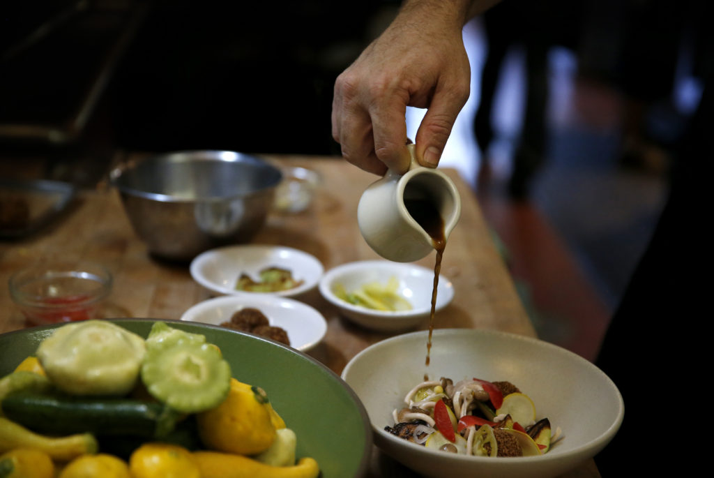 "Chef Joe Zobel pours a a mushroom broth over a dish of squash ""meatballs"", squash crudo and pickled summer vegetables at Peter Lowell's Restaurant in Sebastopol."