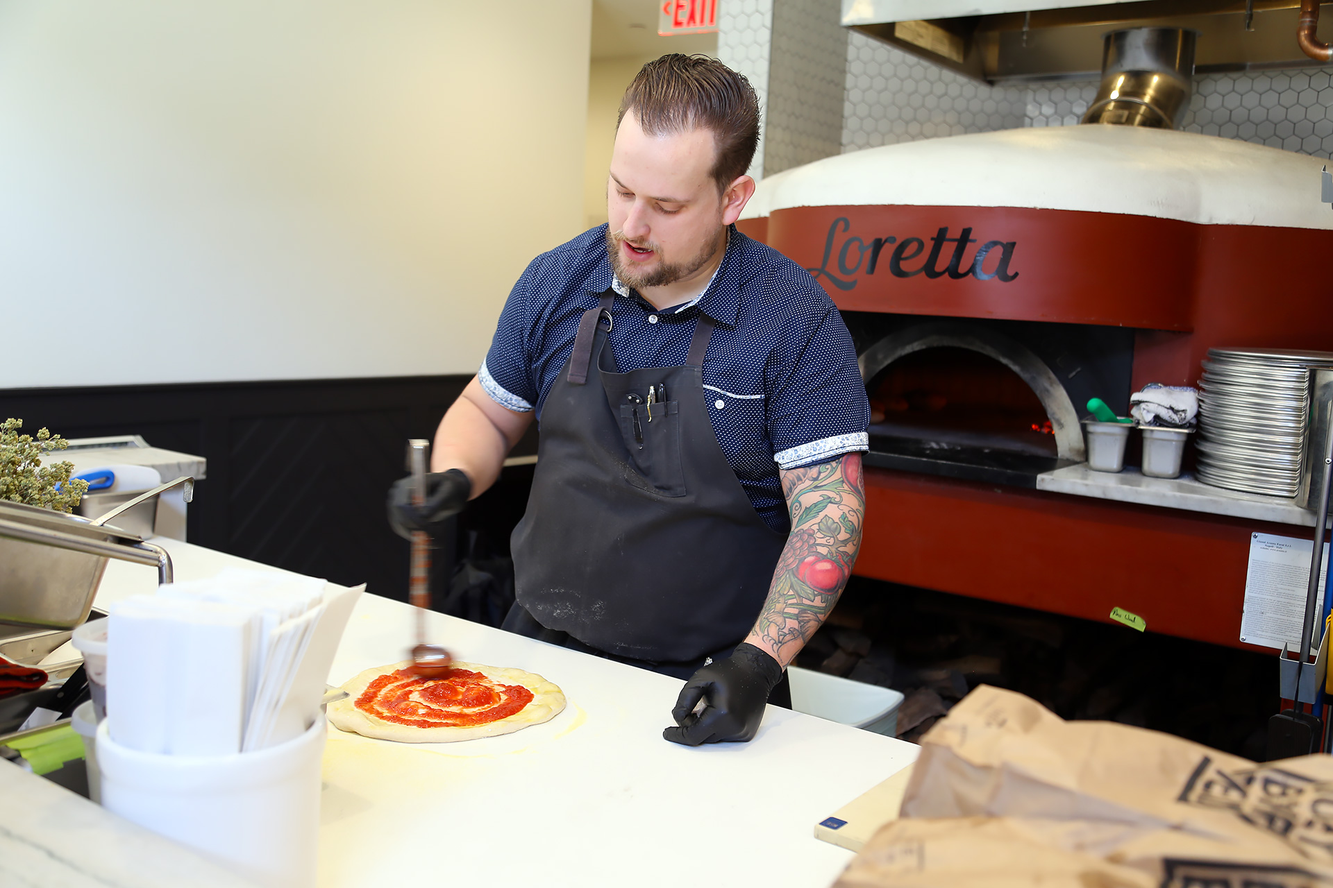 Adding the sauce to the pizze dough