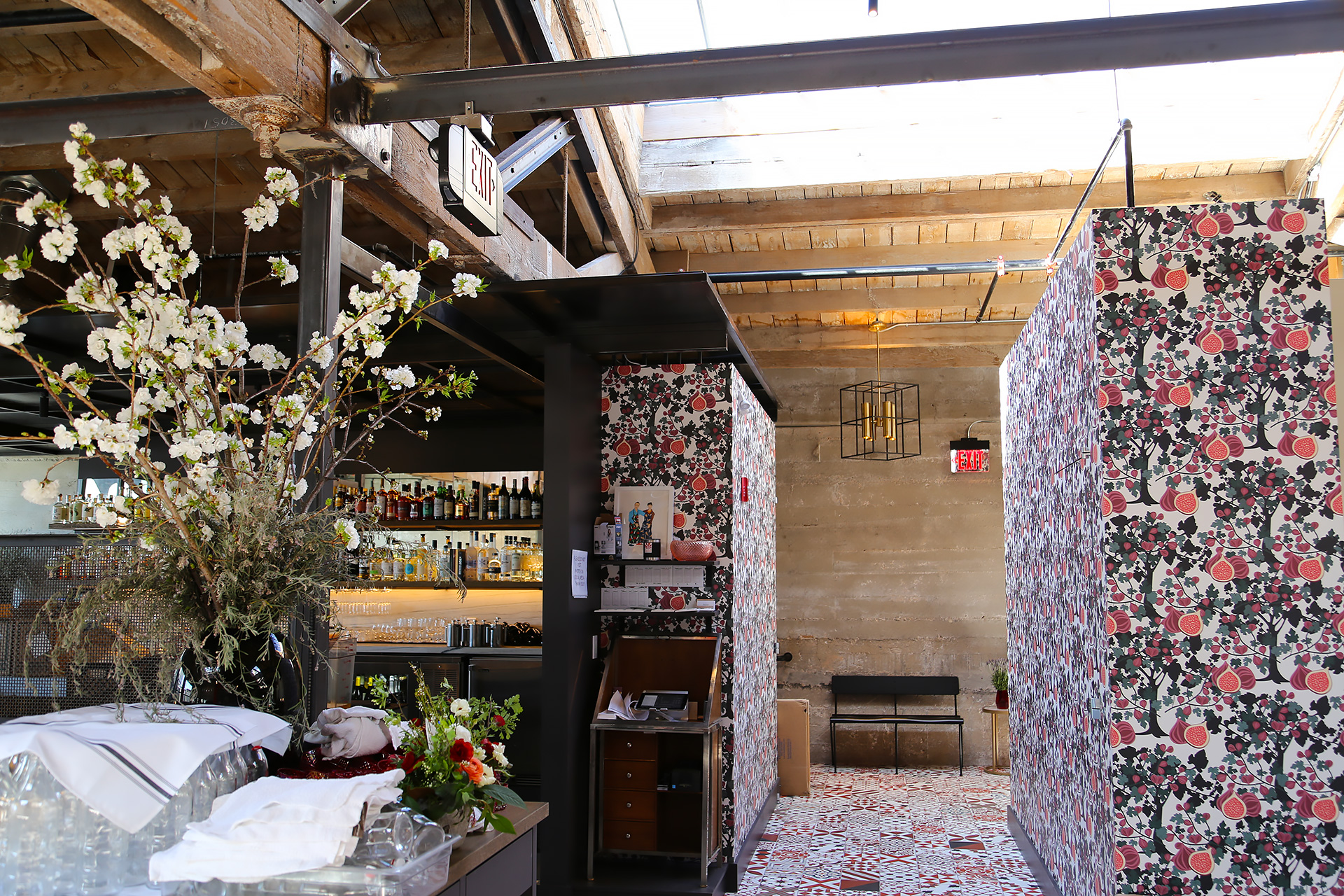 Entryway to Che Fico is adorned with fig wallpaper.
