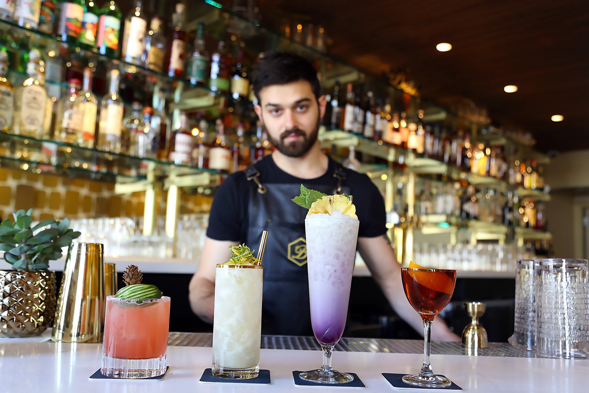 Lead Bartender Emilio Salehi showcases The Beehive cocktails (L to R): Thunderbird, Ipanema Gold, Bikini Drifter, Rising Sun