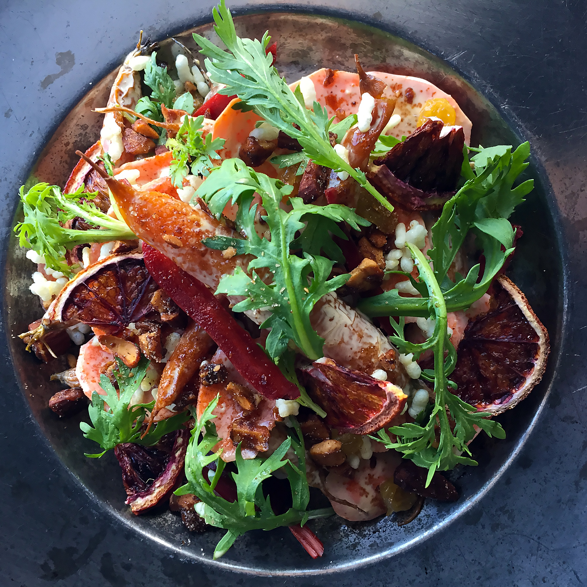 Smoked carrot salad with blood oranges, puffed grains, spiced nuts and chrysanthemum