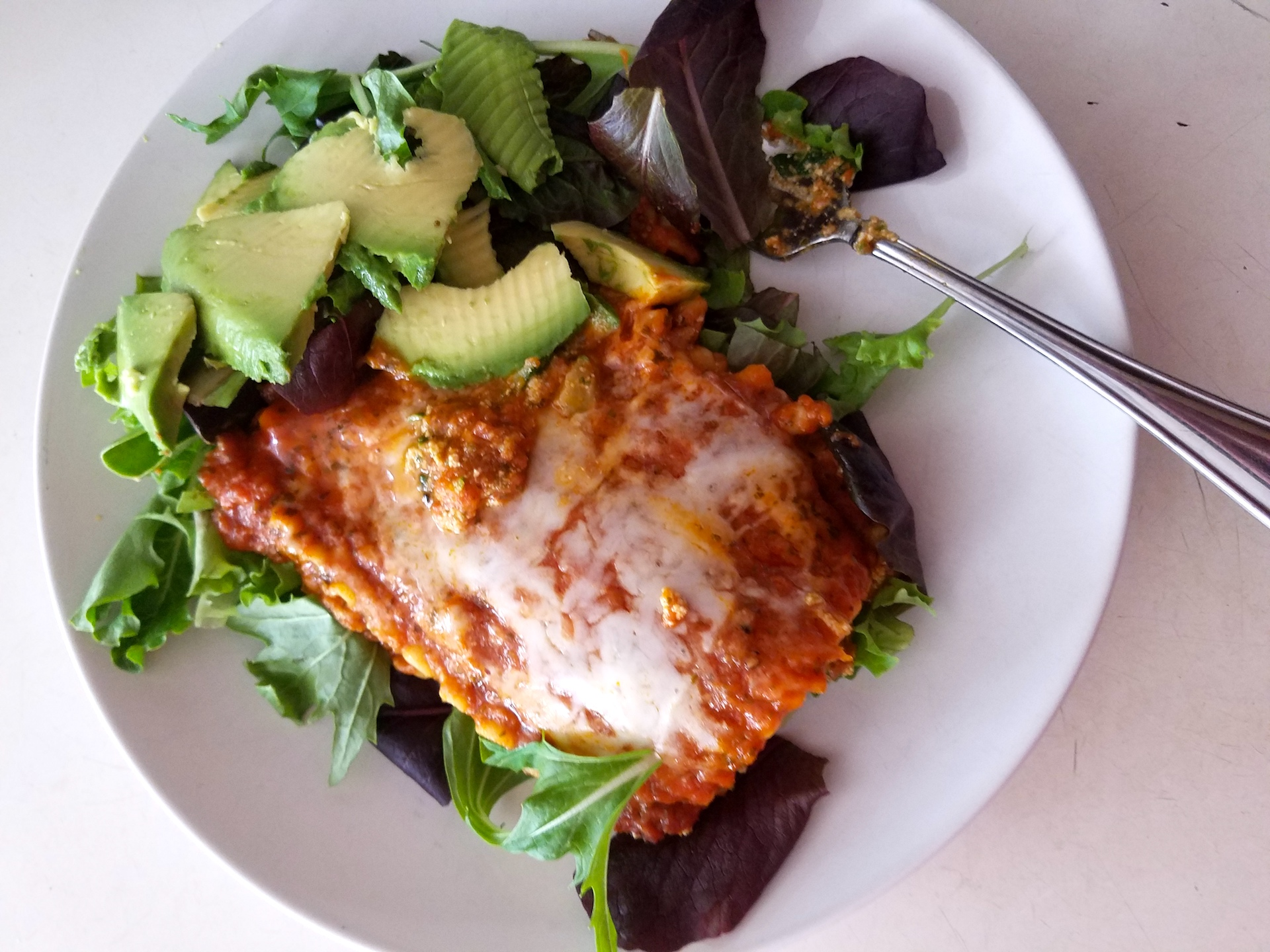Amy's veggie lasagna on a bed of lettuce with avocado.