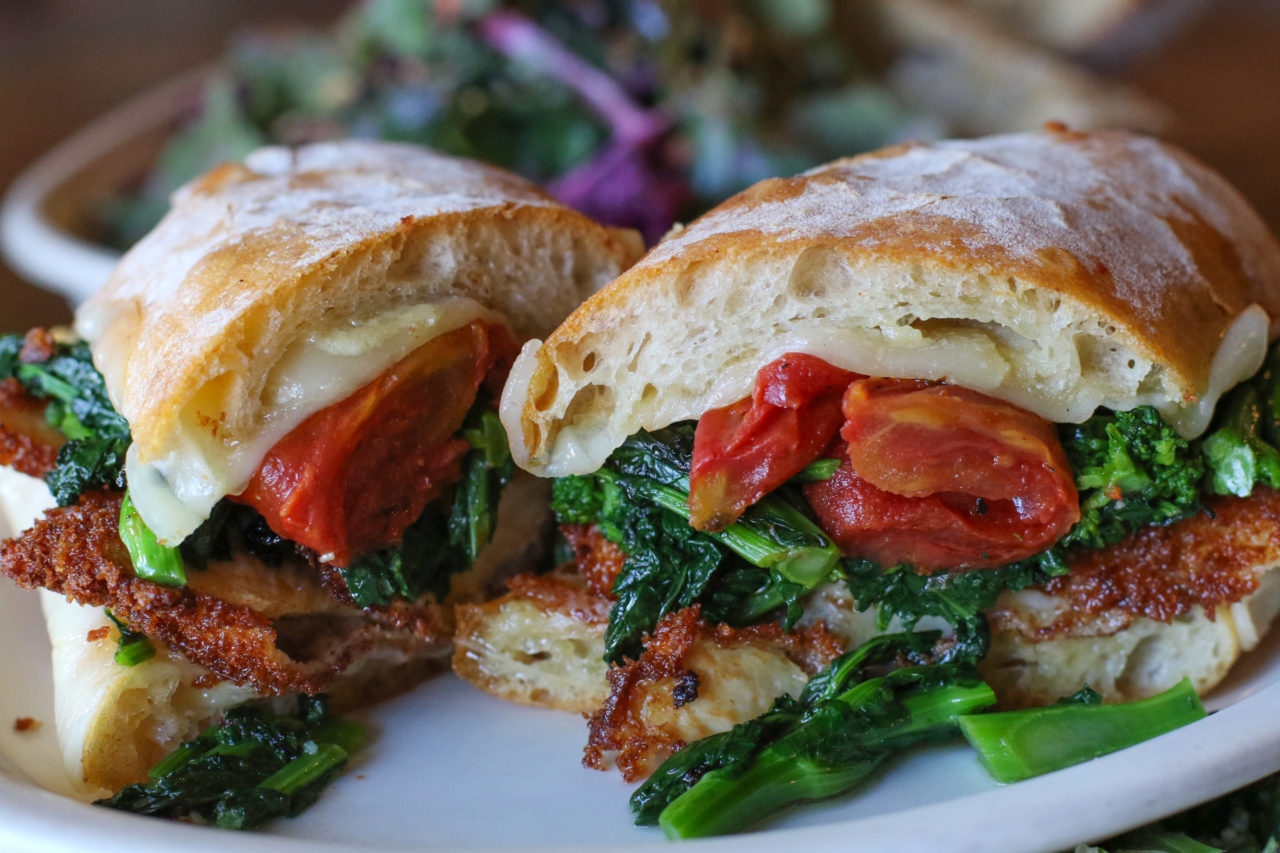 Philly sandwich with fried chicken breast, provolone, oven roasted tomatoes and broccoli rabe.