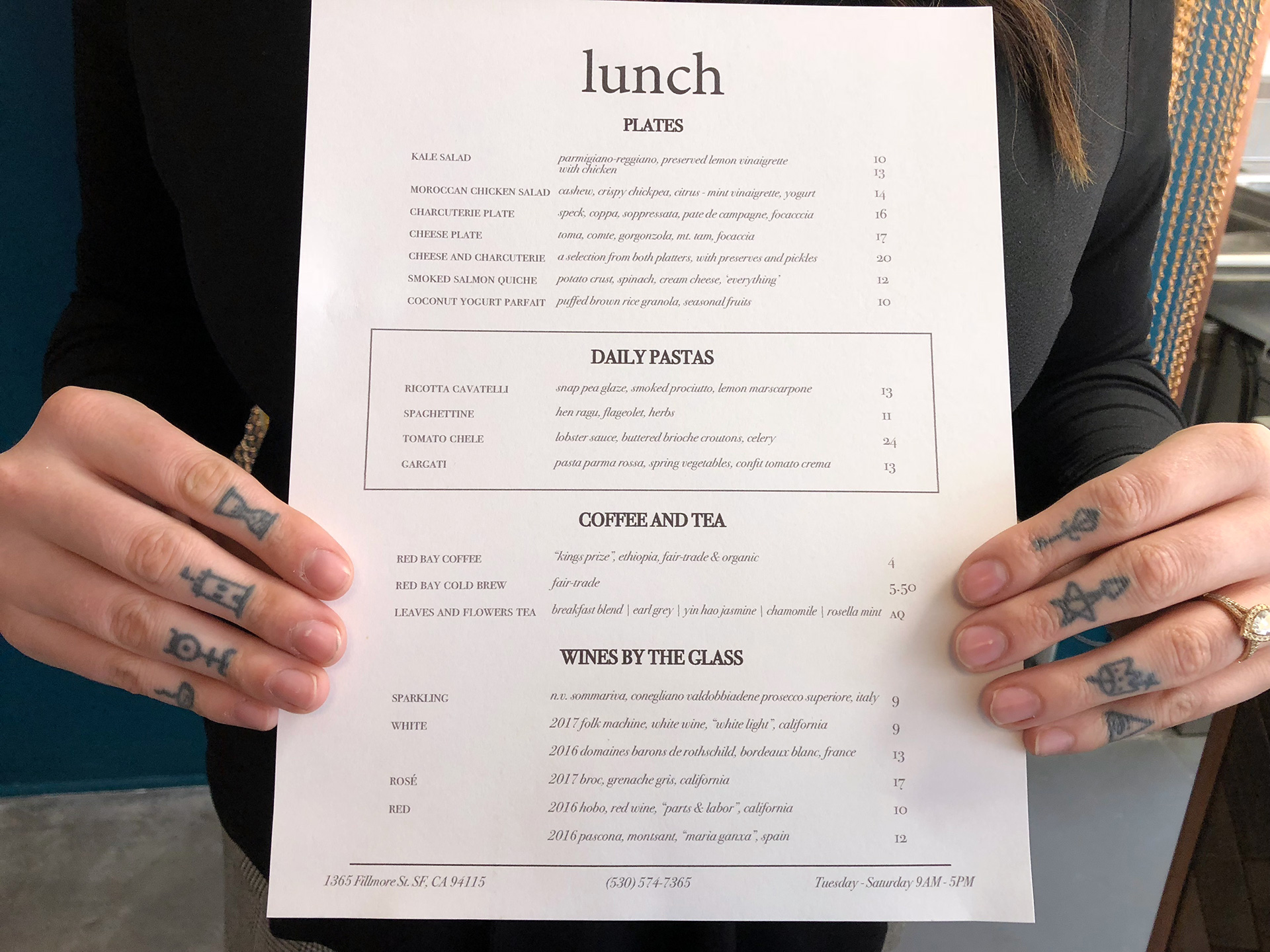 Madison Michael's hands showcase the lunch menu at Merchant Roots