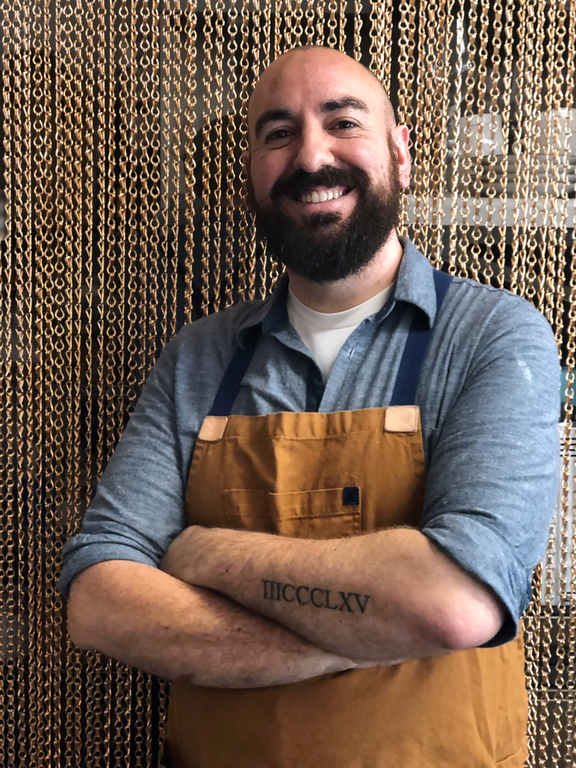 Executive Chef/Proprietor Ryan Shelton shows his recently acquired tattoo that is the address of Merchant Roots in Roman numerals.