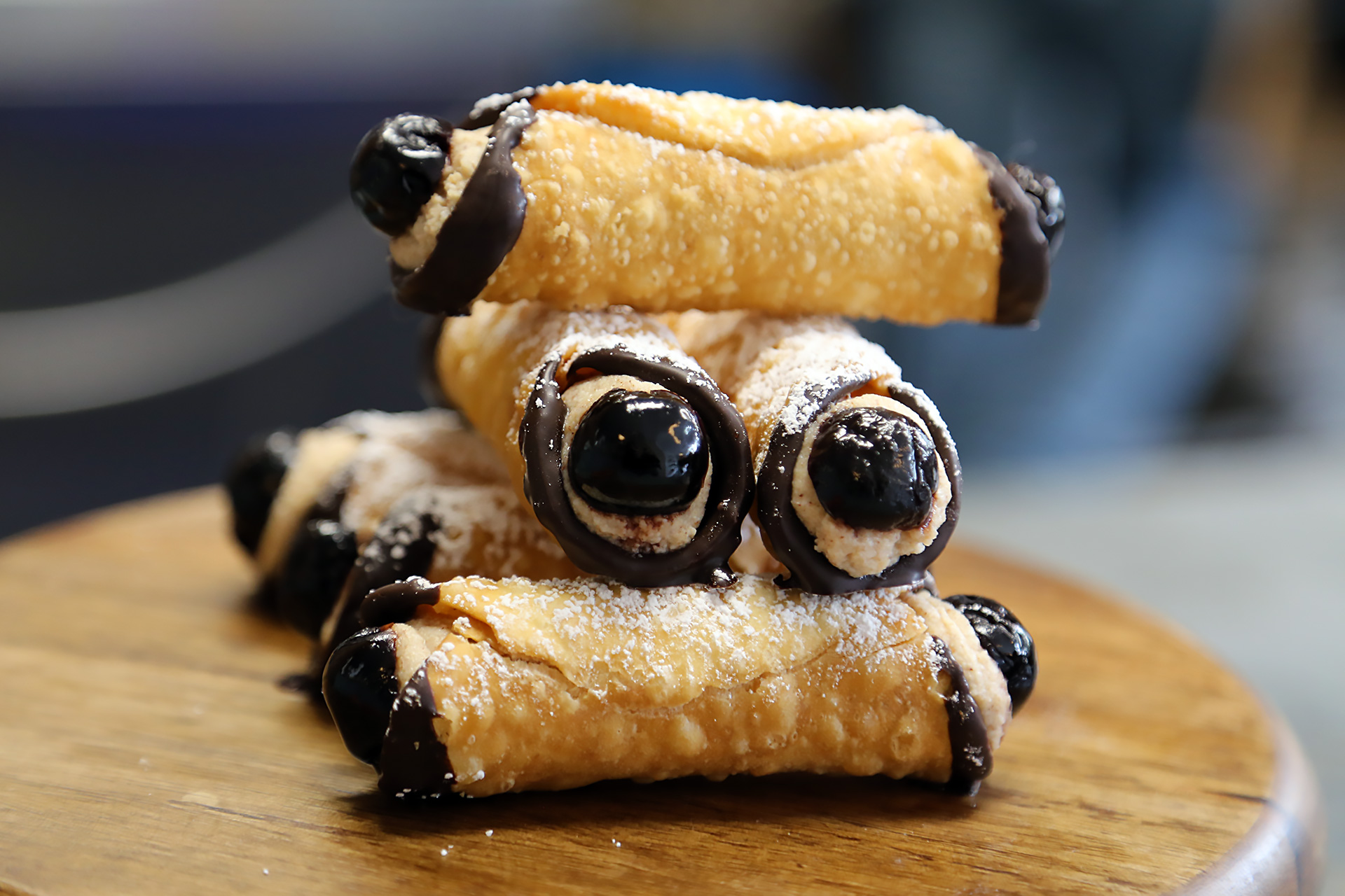 Chocolate-drizzled cannolis with Luxardo cherries dramatically peeking out of both ends.
