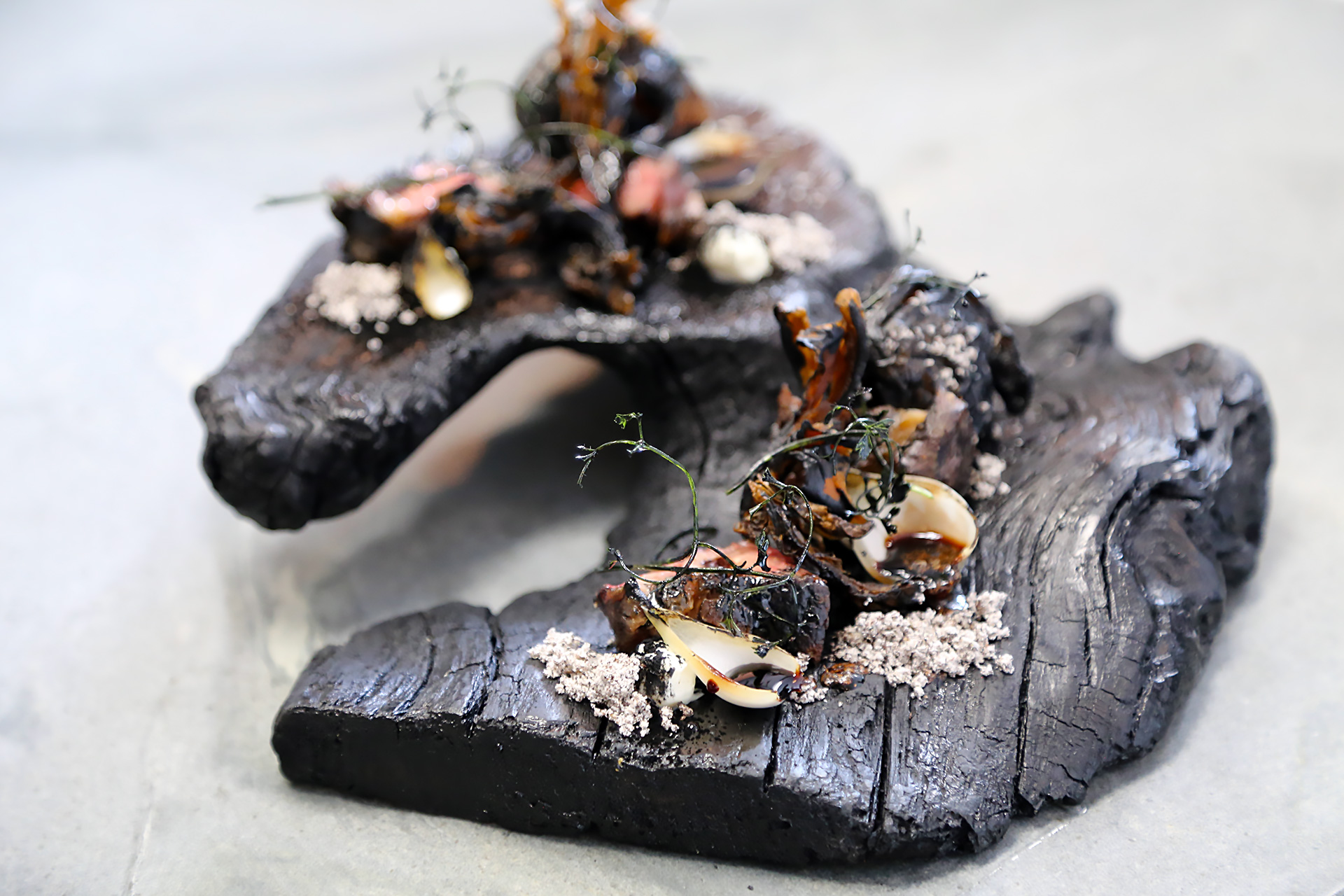 "One ""Elements"" course called ""Fire"" centers on charcoal-grilled dry-aged New York steak, offset by charred pearl onions, crispy maitake mushrooms, leek ash and sunchoke ""coal."""