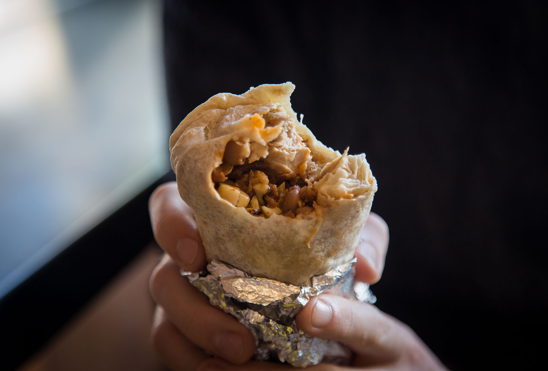 The inside of the Fried Chicken Burrito, and a glimpse of a crispy piece of Fried Chicken inside.