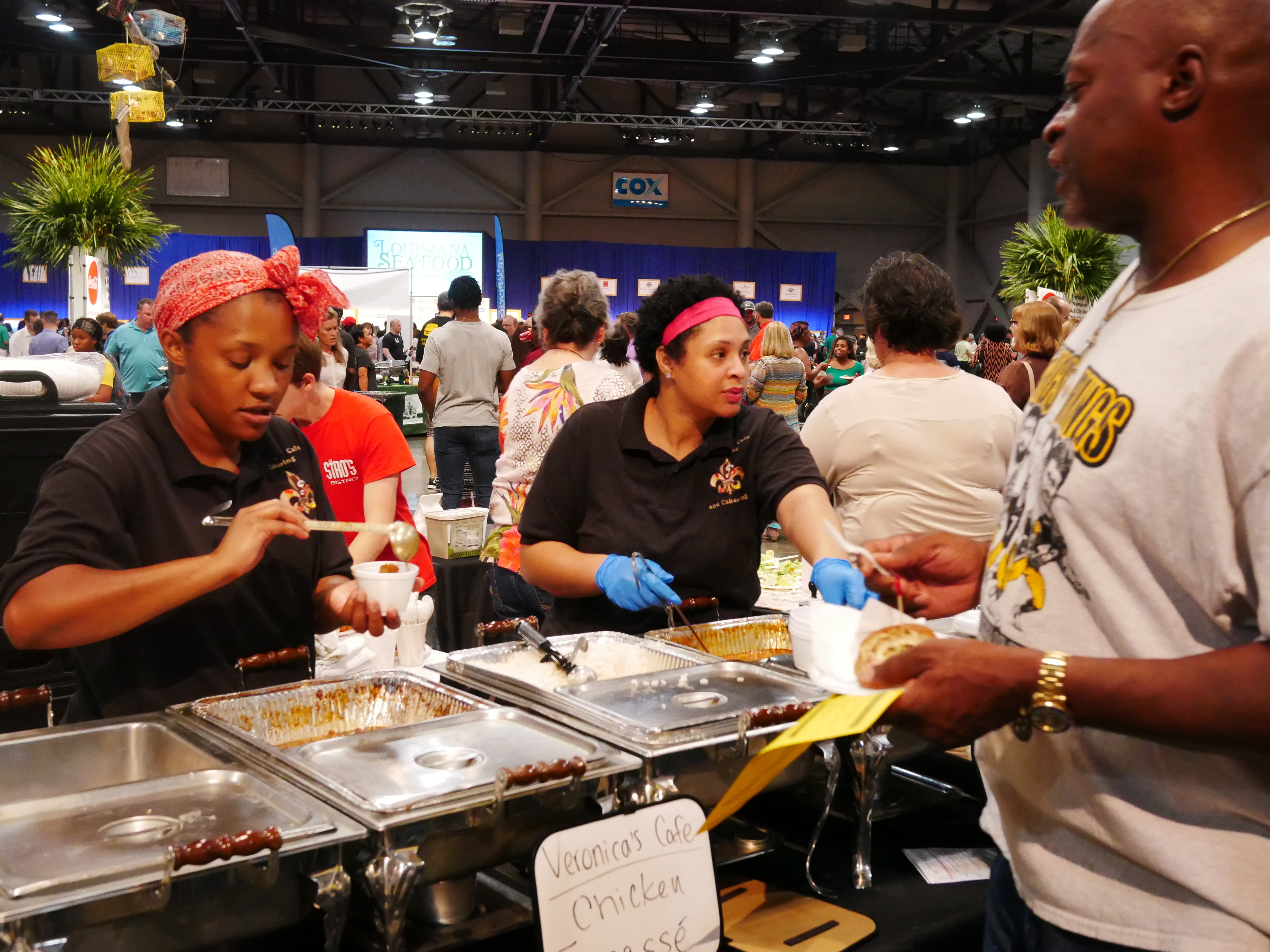 """Restaurant workers dole out chicken fricassee at the """"Taste of EatLafayette"""" festival in the sprawling Cajundome arena in Lafayette, Louisiana. Locals say Bourdain captured the subtleties of their culture and cuisine, even if at times some thought he overemphasized alcohol."""