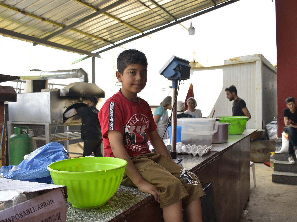 Bashar, sits on a table for prepping meals in the Ramadan Kitchen.