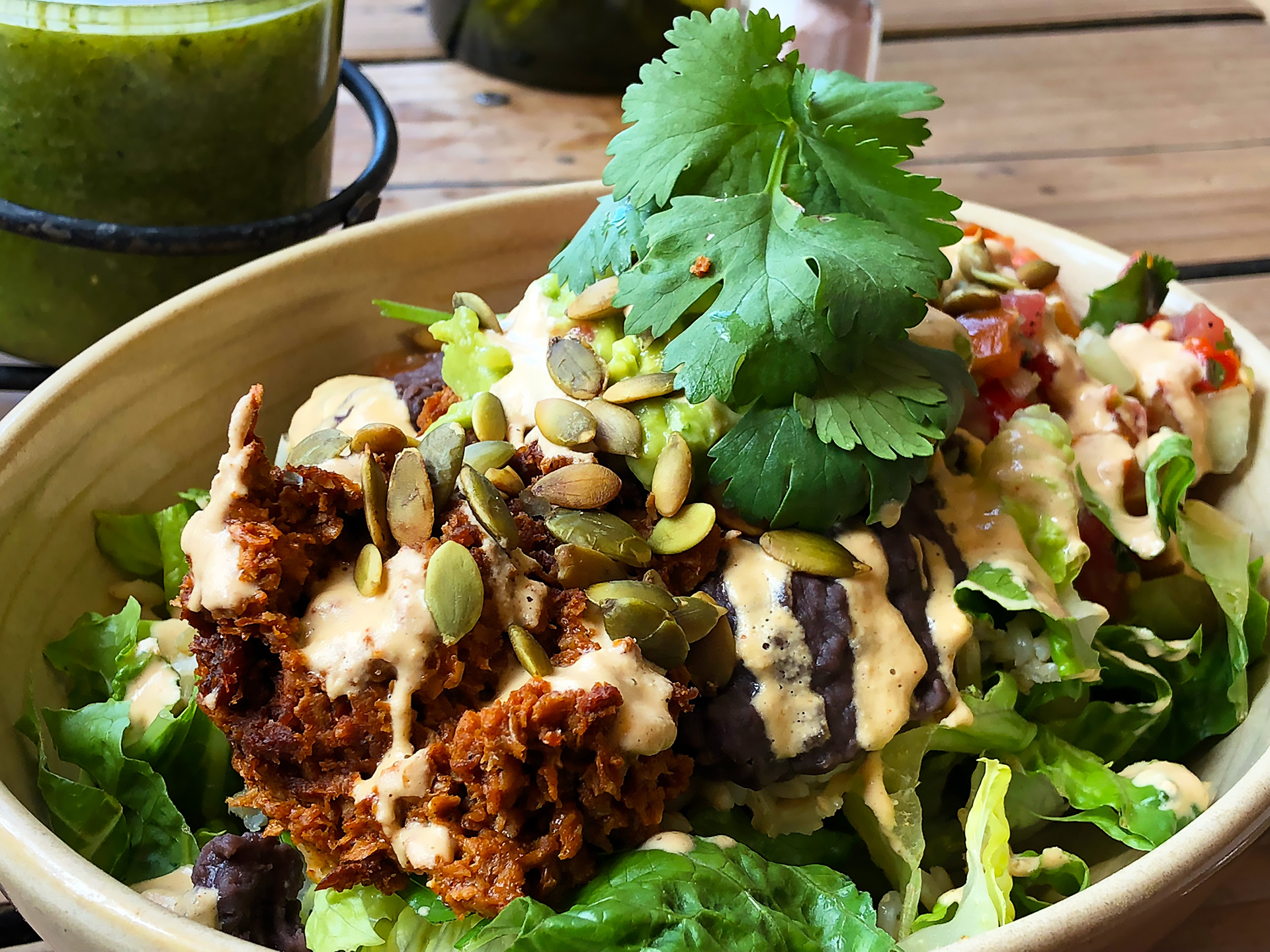 Bowl Uno: Tempeh chorizo, black beans, guacamole, brown rice and pico de gallo served on a bed of romaine and topped with nacho cashew cheese and pepitas. ($15)