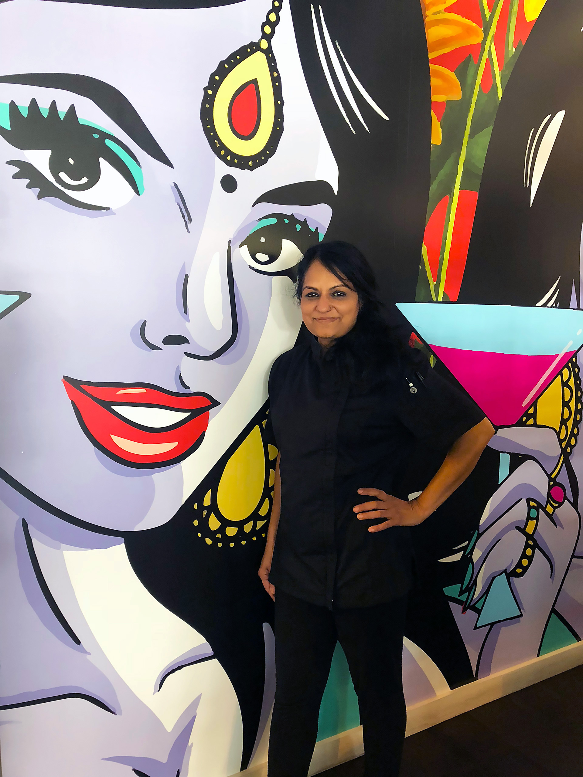 Chef and Partner Heena Patel in front of pop-art mural by HateCopy's Maria Qamar