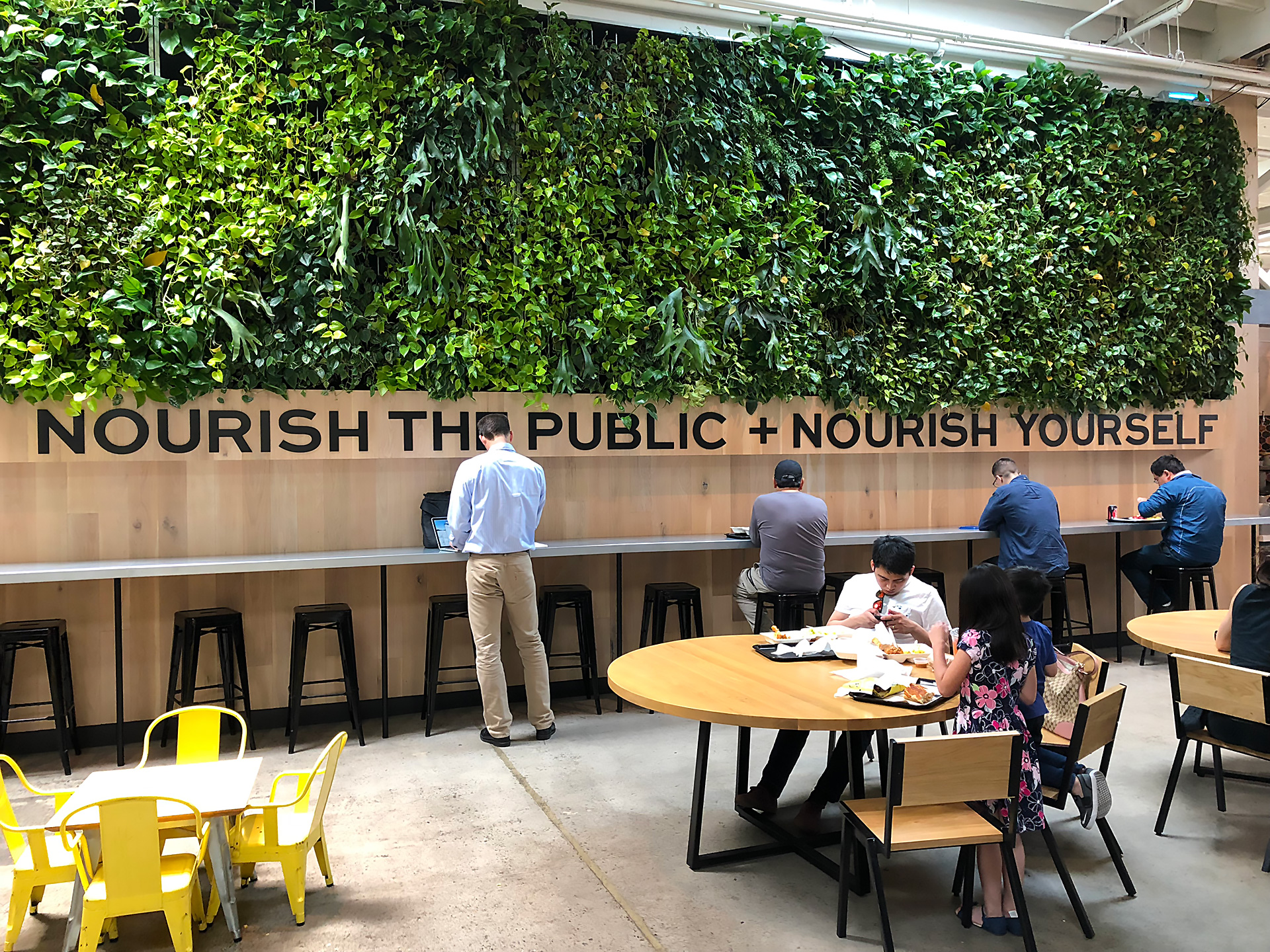 """Nourish The Public + Nourish Yourself"" signage at The Emeryville Public Market next to Minnie Bell's kiosk."