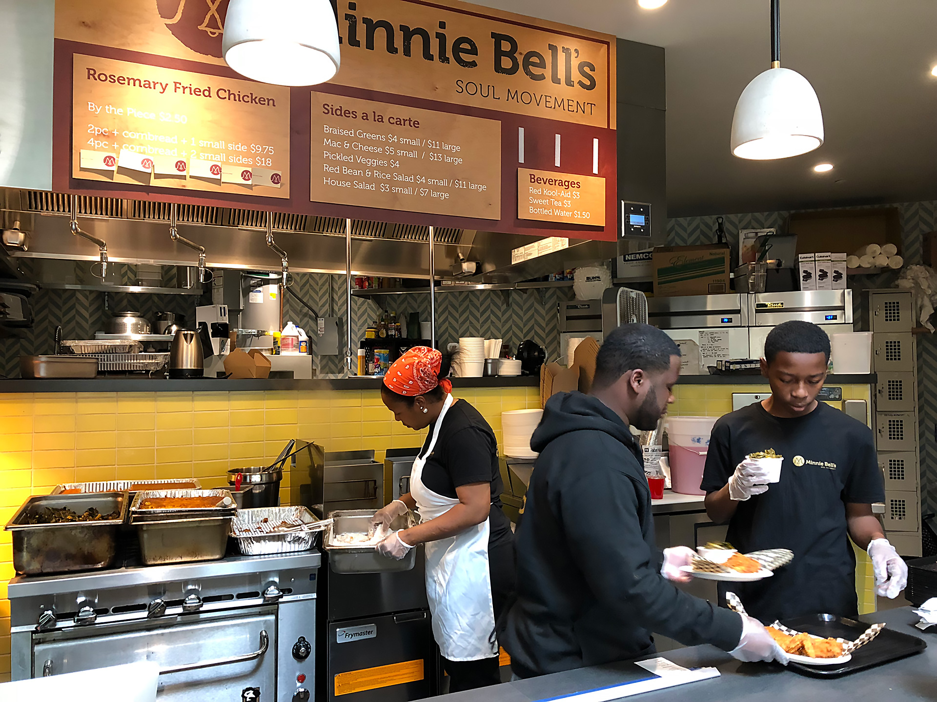 Fernay McPherson, fellow employee and Fernay's son Eric (R) working at the Minnie Bell's kiosk.