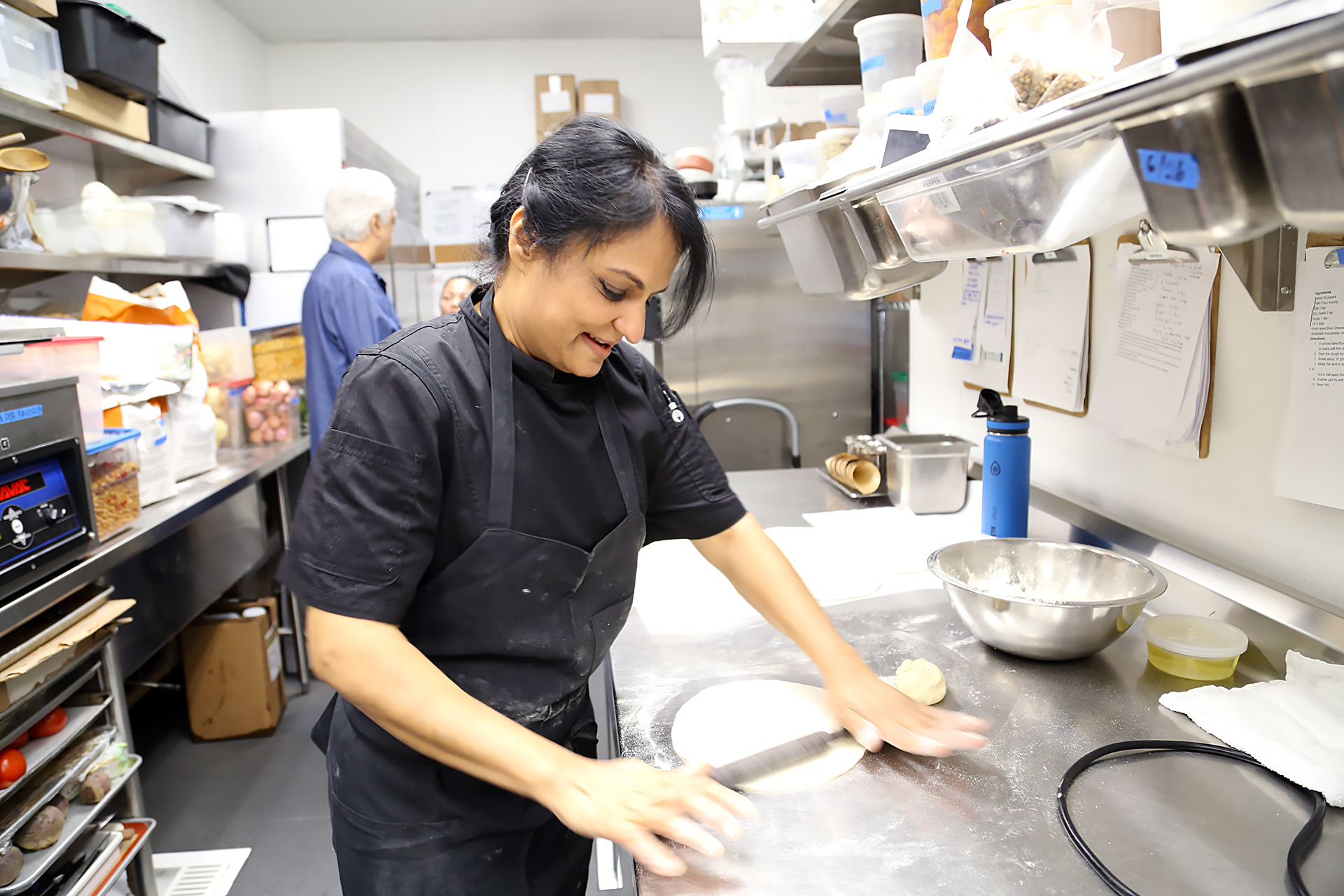 Heena Patel rolls dough for flatbread in back kitchen.