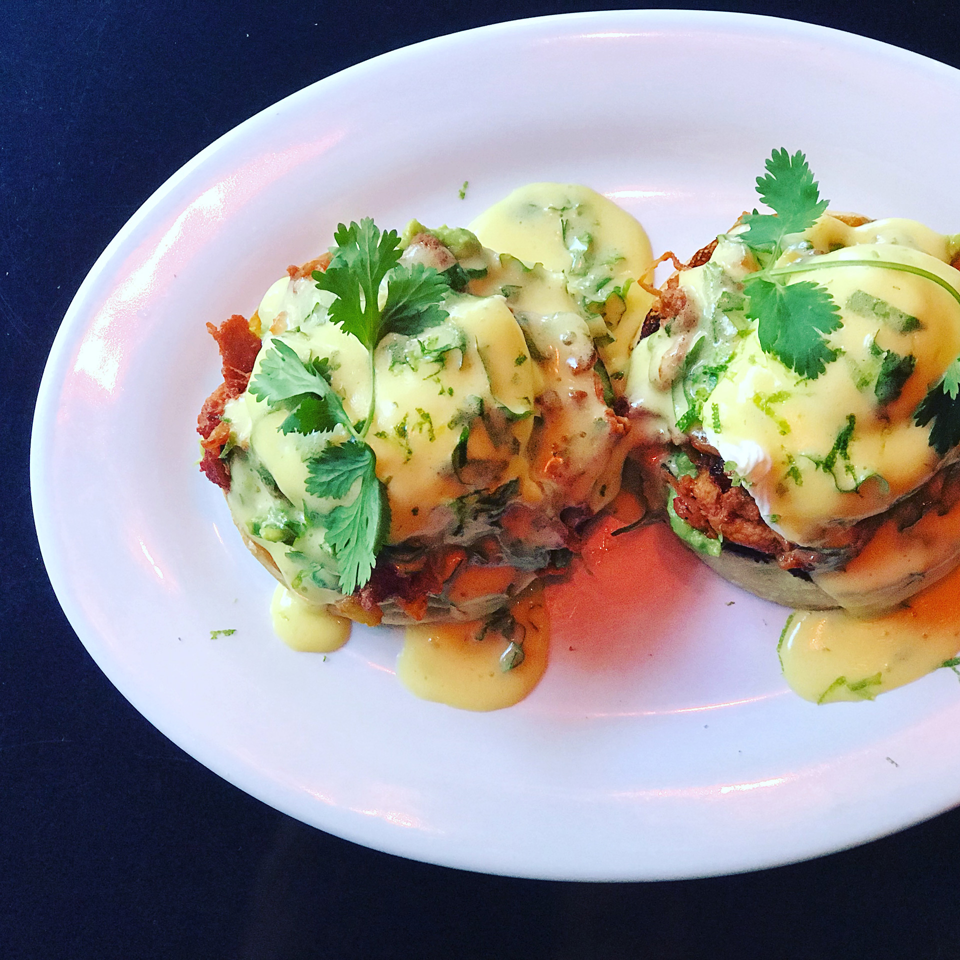 Benedict Brunch at Foxsister includes The Mission version with al pastor pork shoulder, avocado, lime, and hollandaise.