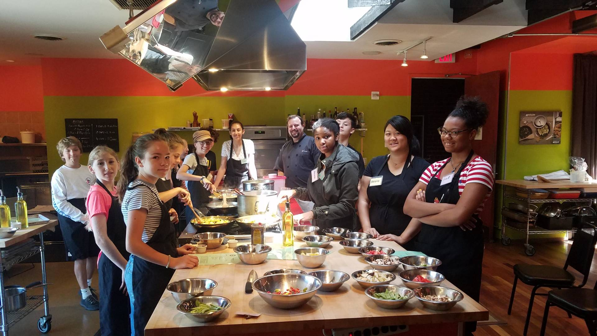 Students pose during a cooking class with Kitchen on Fire.