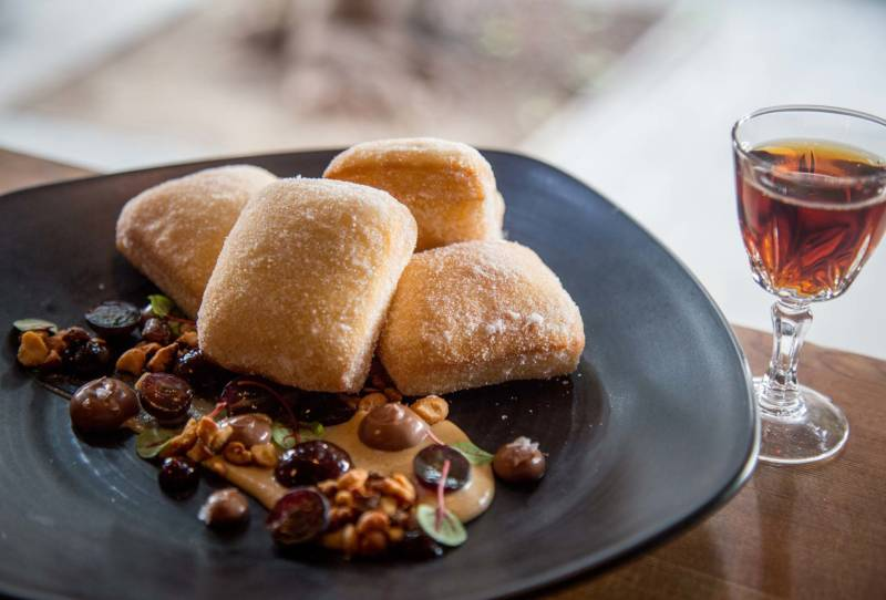 The classic PB&J sandwich is reimagined as fluffy beignets with a peanut butter sauce with concord grapes.