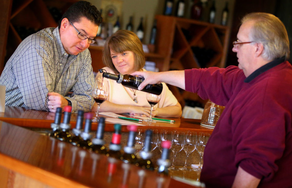 Tasting room manager Gary Gross, right, pours a 2009 Vintage Port for Bernadette and Eduardo Gamez, from Chandler, Arizona, at Pedroncelli Winery, in Geyserville on Thursday, November 13, 2014.