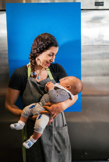 Reem Assil holding her baby at Reem's California.