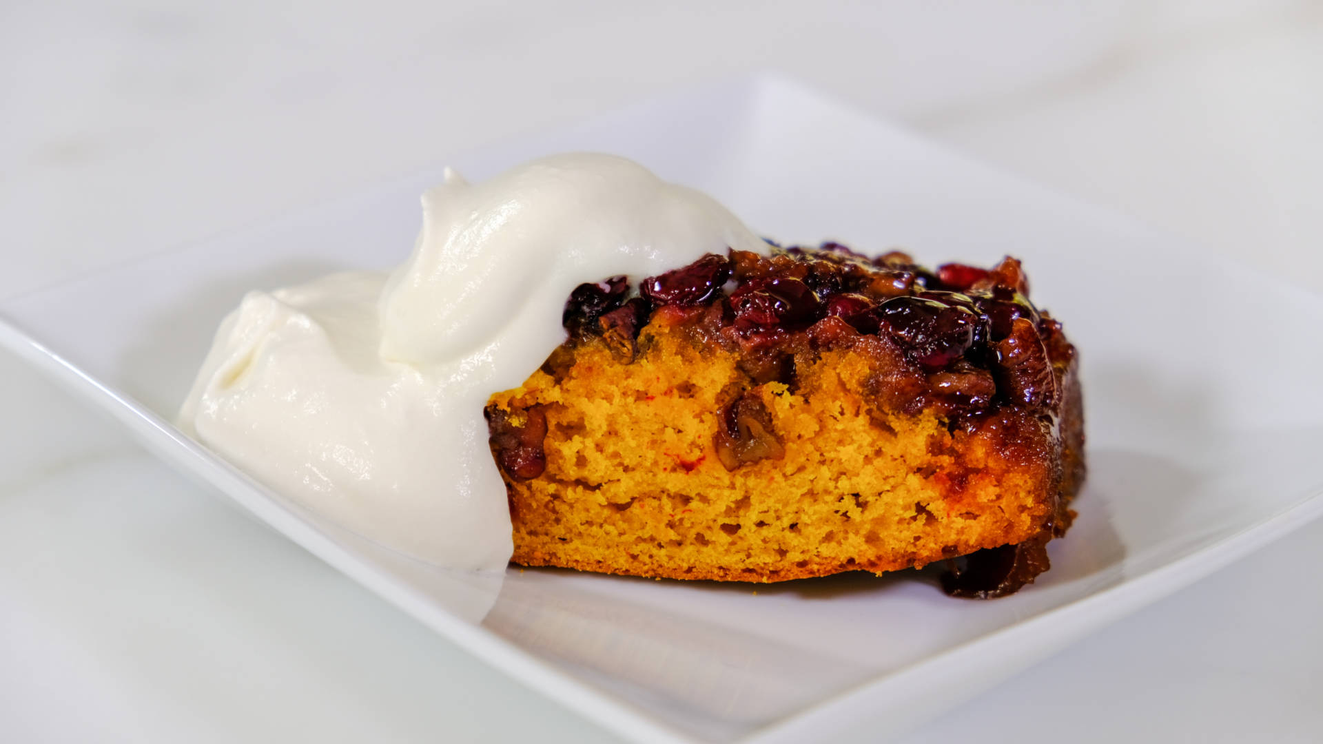 Emily Luchetti's Pumpkin Upside-Down Cake topped with fresh whipped cream.