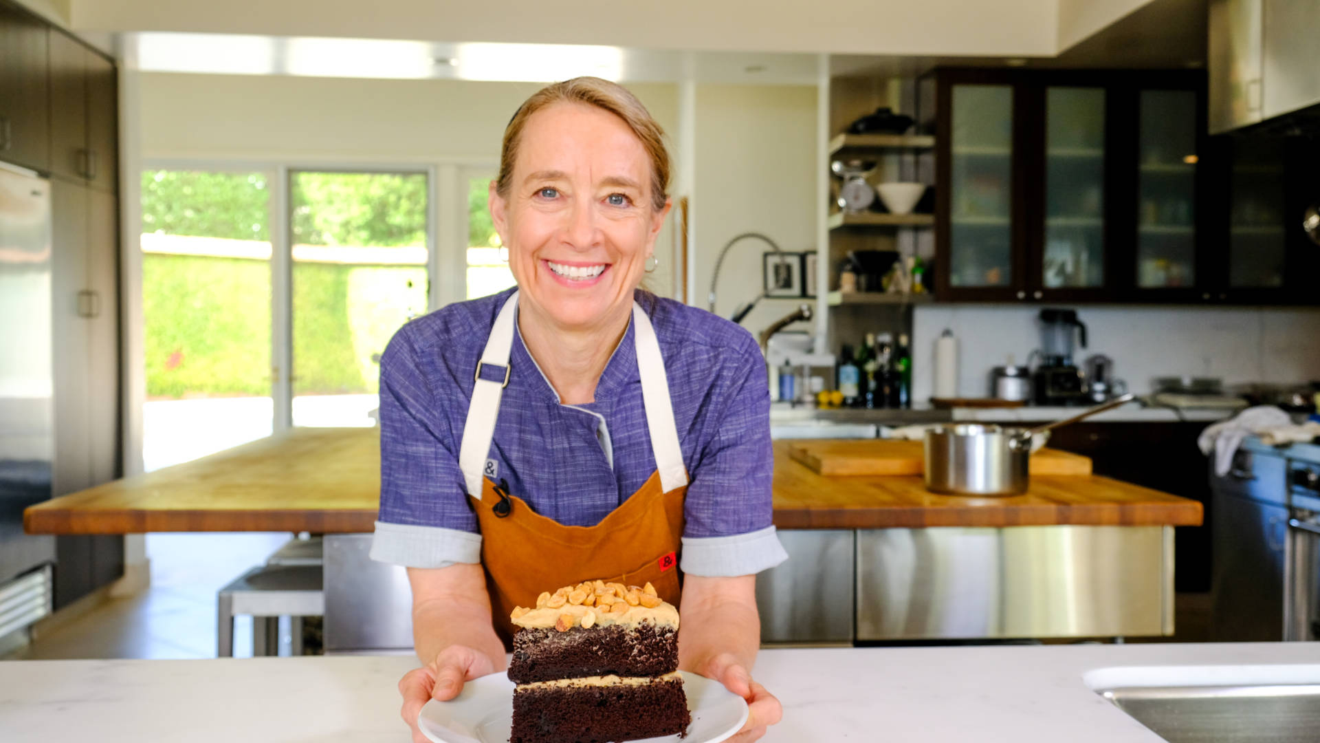 Chef Emily Luchetti with a slice of her classic chocolate cake topped with peanut butter frosting and honeyed peanuts.