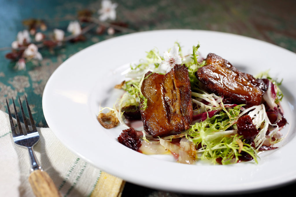 Cherry soffrito pork belly with chicory and crispy shallots by chef Anthony Gallegos at Jimtown Store in Healdsburg, California on Thursday, February 23, 2017.