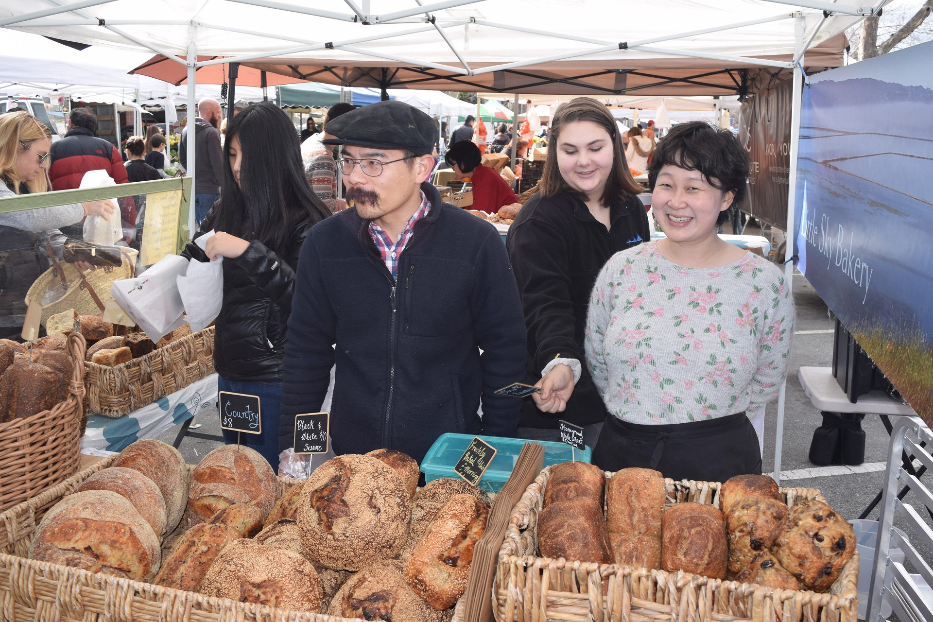 Crowds are lined up in front of the Little Sky booth at the Menlo Park farmers market before it opens and snag everything available.  Left, Yan Xu; right, Tian Mayimin.
