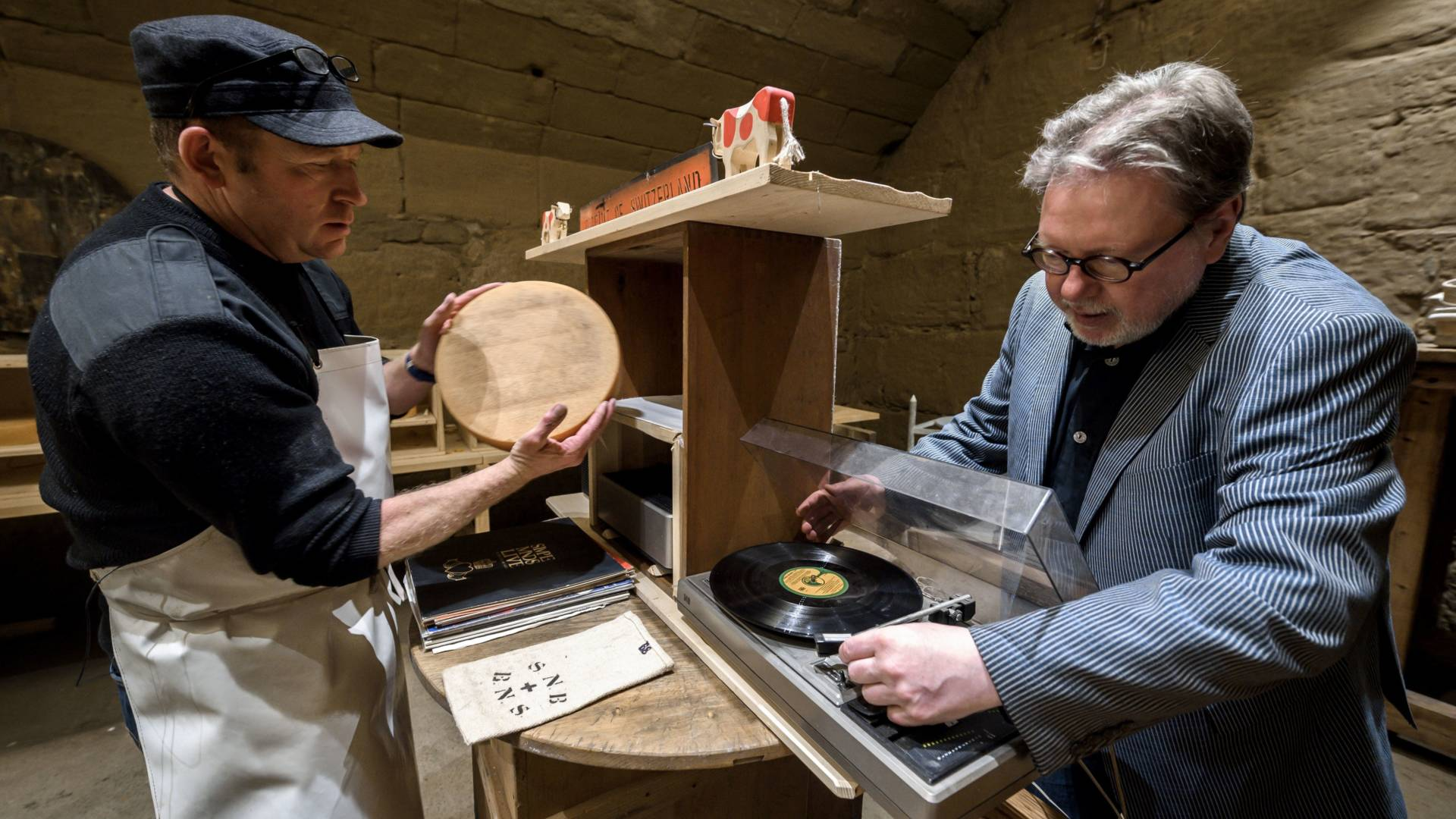 Swiss cheesemaker Beat Wampfler, left, and director of the Music Department at University of the Arts in Bern, Michael Harenberg pose with a vinyl record and a wheel of Emmental.