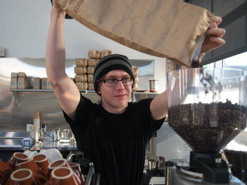 evan gilman pouring coffee beans