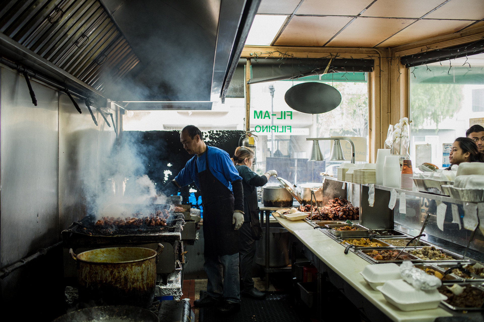 Arnold Custodio and Vicky de Leon behind the counter preparing barbecue inasal at Fil-Am Cuisine on School Street in Daly City.
