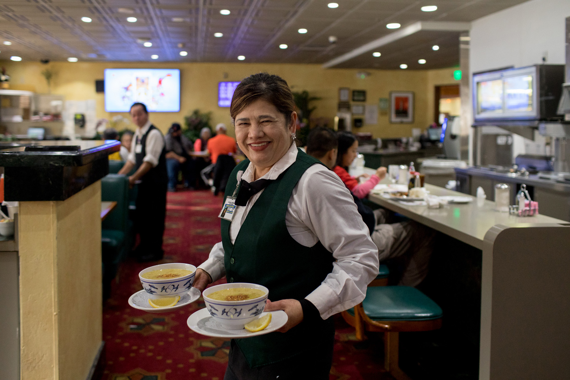 Lucky Chances casino has an all-ages cafe that serves Filipino classics along with American diner staples. Server Melissa Deguzman carries goto (beef tripe and garlic rice porridge) to customers.