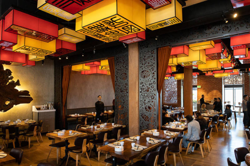 Geometric lanterns and lotus patterns in the laser-cut dividing walls put a modern twist on classic Chinese themes at Palette Tea House.