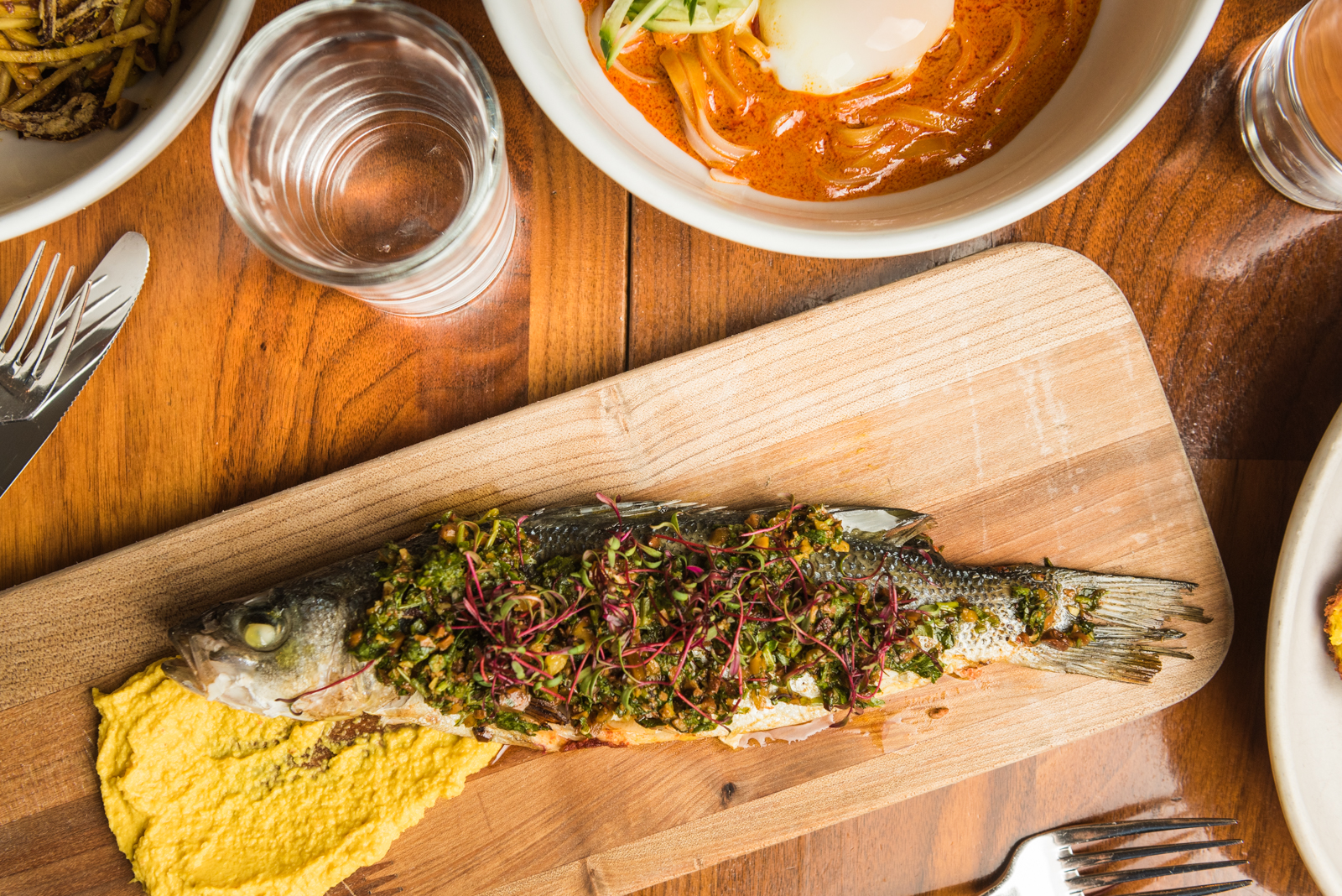Wood-Fire Roasted Whole Branzino with sambal marinade, turmeric cauliflower puree and pistachio sambal.