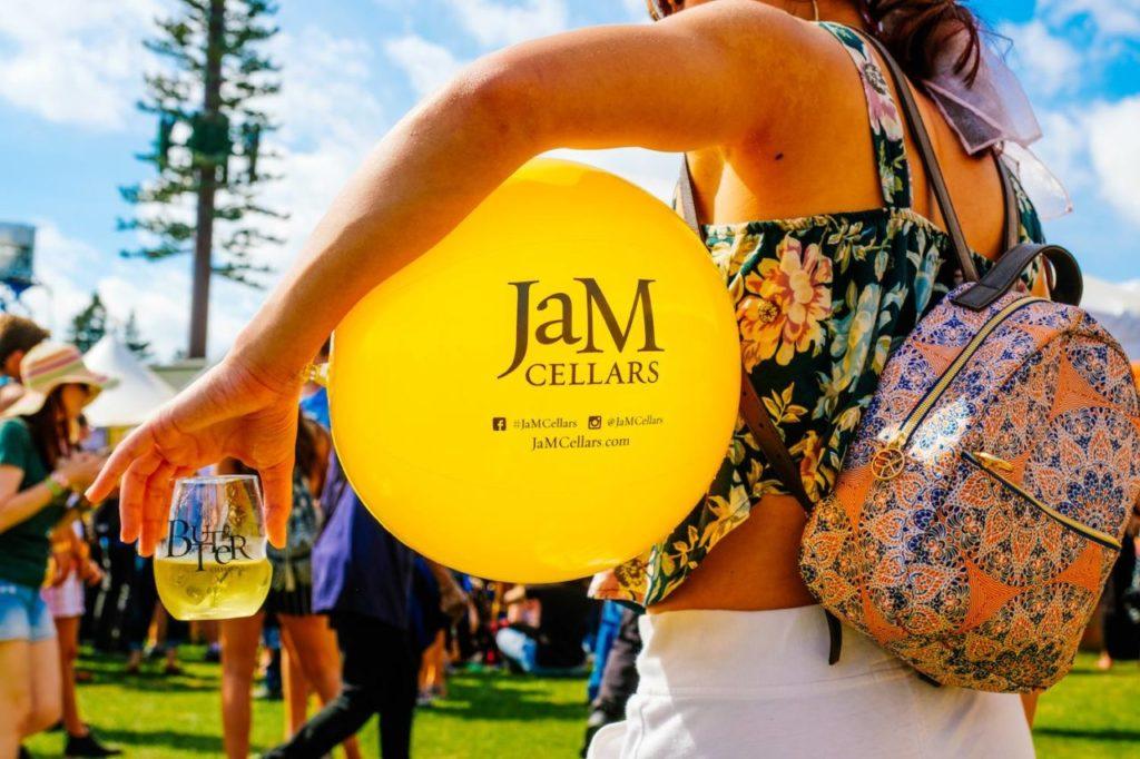 BottleRock attendee with JaM Cellars balloon and wine.