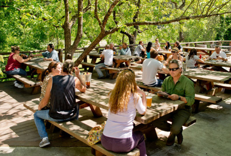 Guests enjoying cold drinks on the patio overlooking the Russian River at Stumptown Brewery.